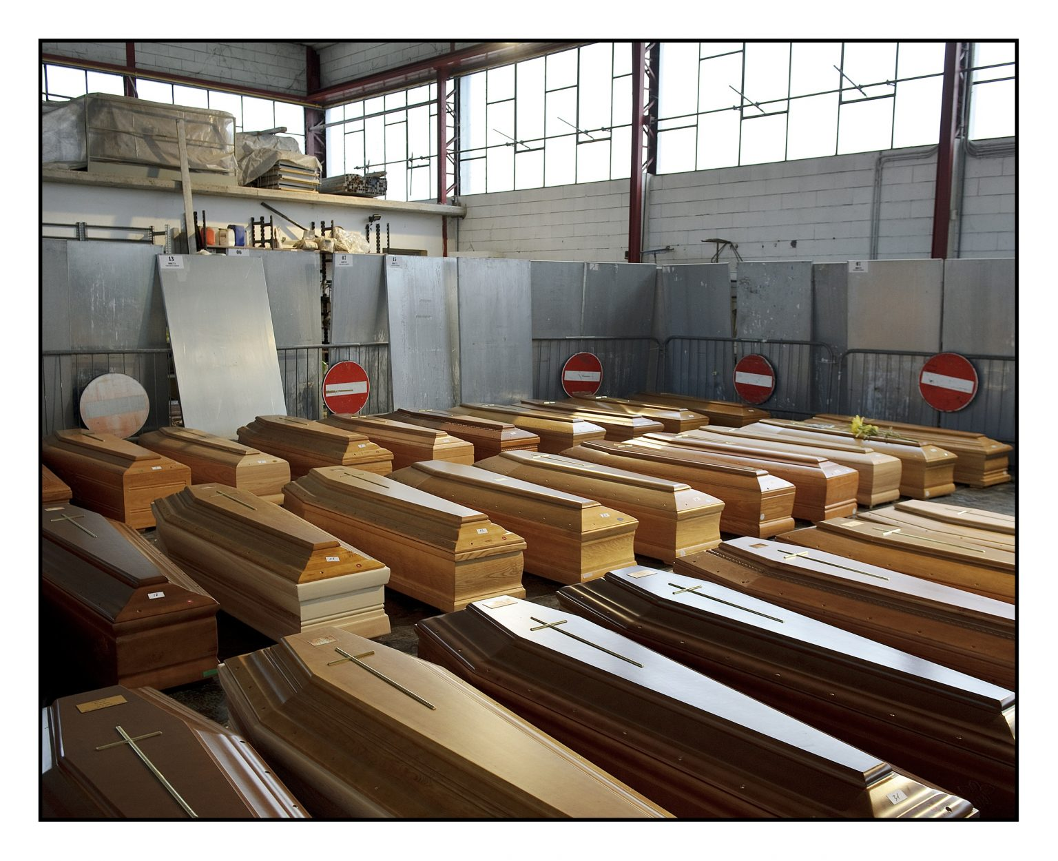 Coffin depots. The coffins that have flowed into the emergency depot of Ponte San Pietro, where the dead people from the western part of the Bergamo province are collected. There are about 30 coffins waiting to be transported out of the province, to the available crematory ovens. Ponte San Pietro, March 26th 2020
