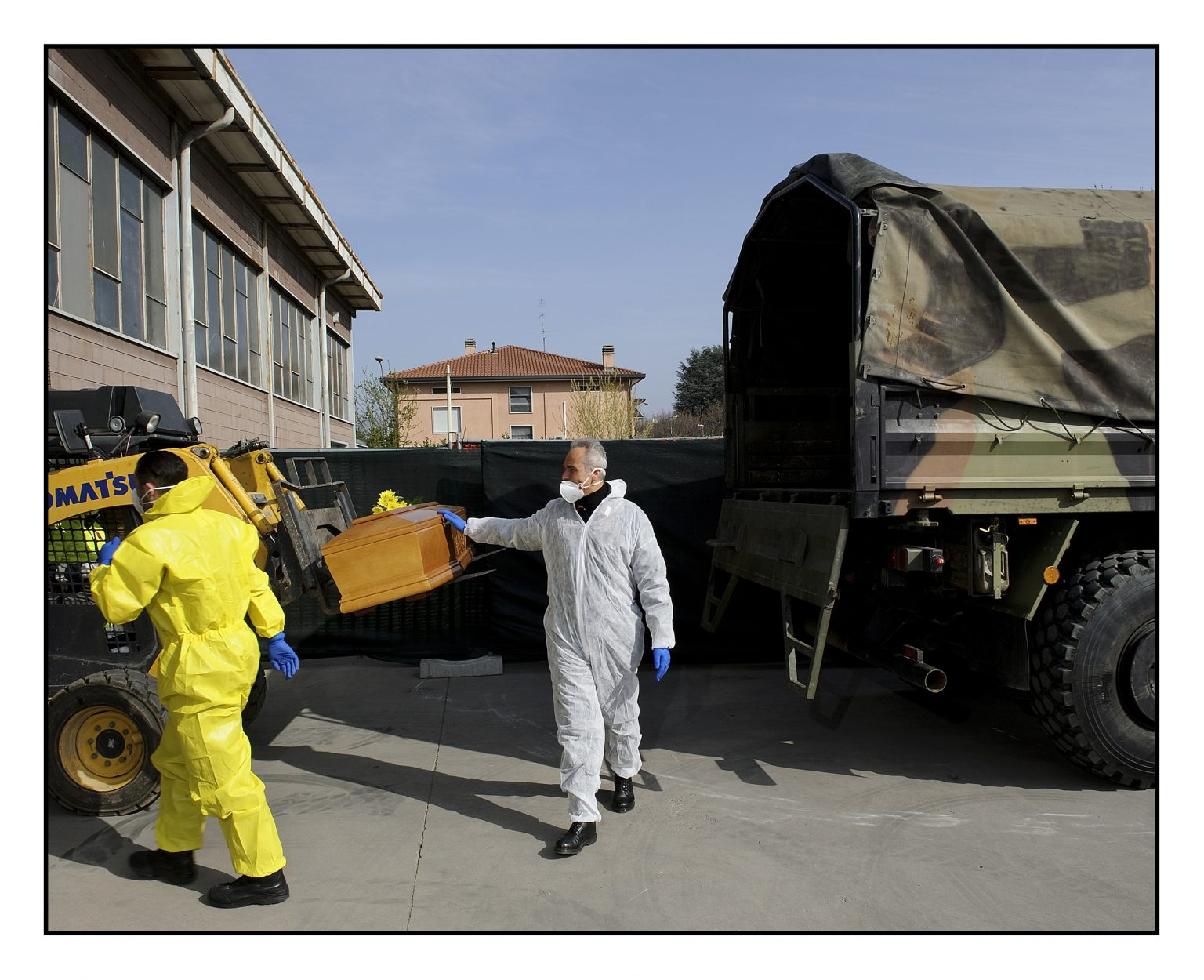 Coffin depots in Bergamo area. The coffins that have flowed into the emergency depot of Ponte San Pietro, where the dead people from the western part of the Bergamo province are collected. A Carabiniere touches a coffin just loaded onto a truck, for a moment of prayer. The Esercito Italiano (Italian Army) carry out the loading operations for the transport out of the province, to the available crematory ovens. Ponte San Pietro, March 28, 2020