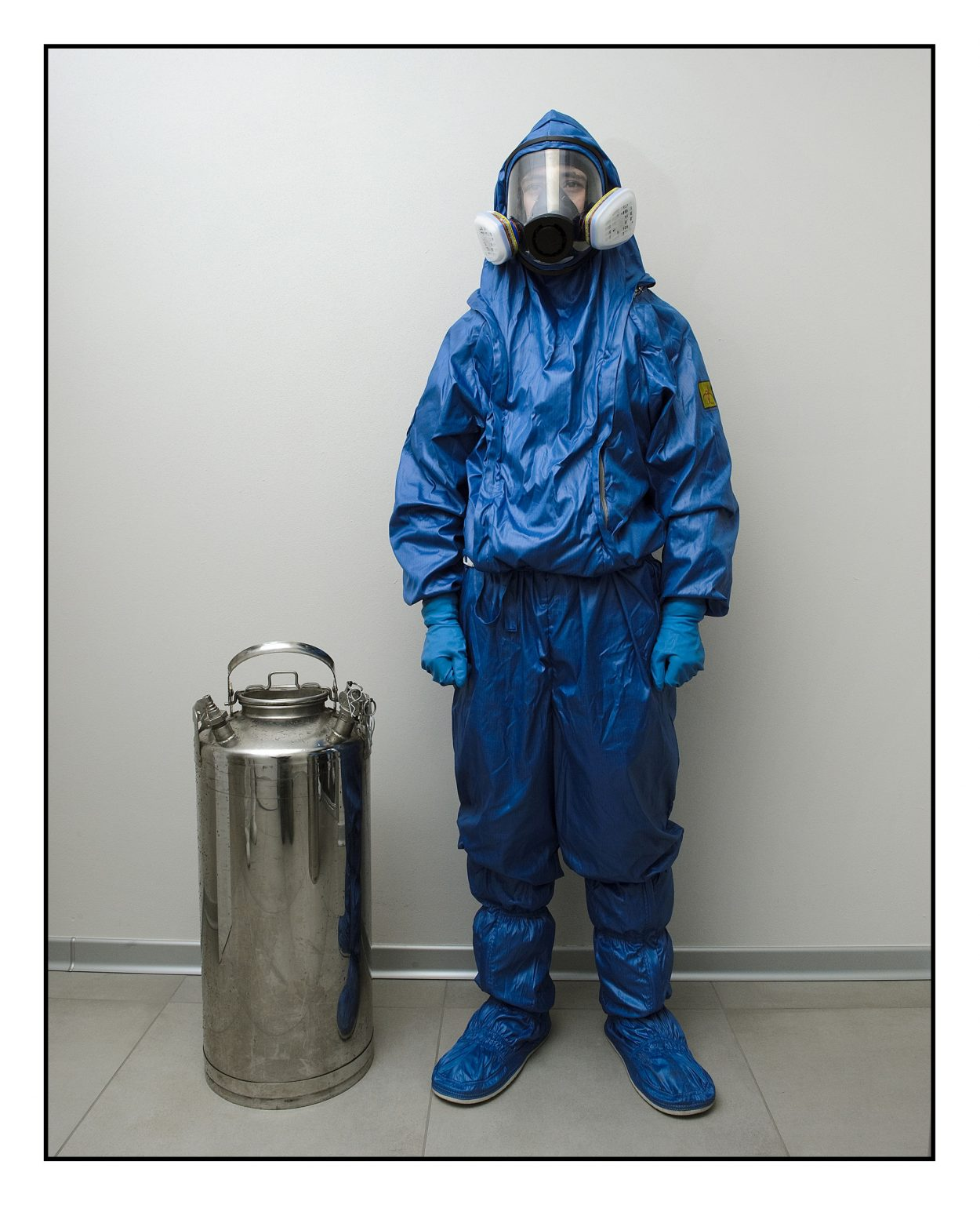 """A soldier of the Special Chemical, Bacteriological, Radioactive and Nuclear Defense Forces of the Russian army waiting for the elevator in the hallway of the nursing home, to carry equipment for sanitation operations into the rooms. The operations are carried out in collaboration with the """"Cremona"""" Biological and Chemical Nuclear Defense Regiment (CBRN) of the Italian army. Ponte San Pietro, Fondazione Casa di Riposo Onlus, April 1st 2020"""