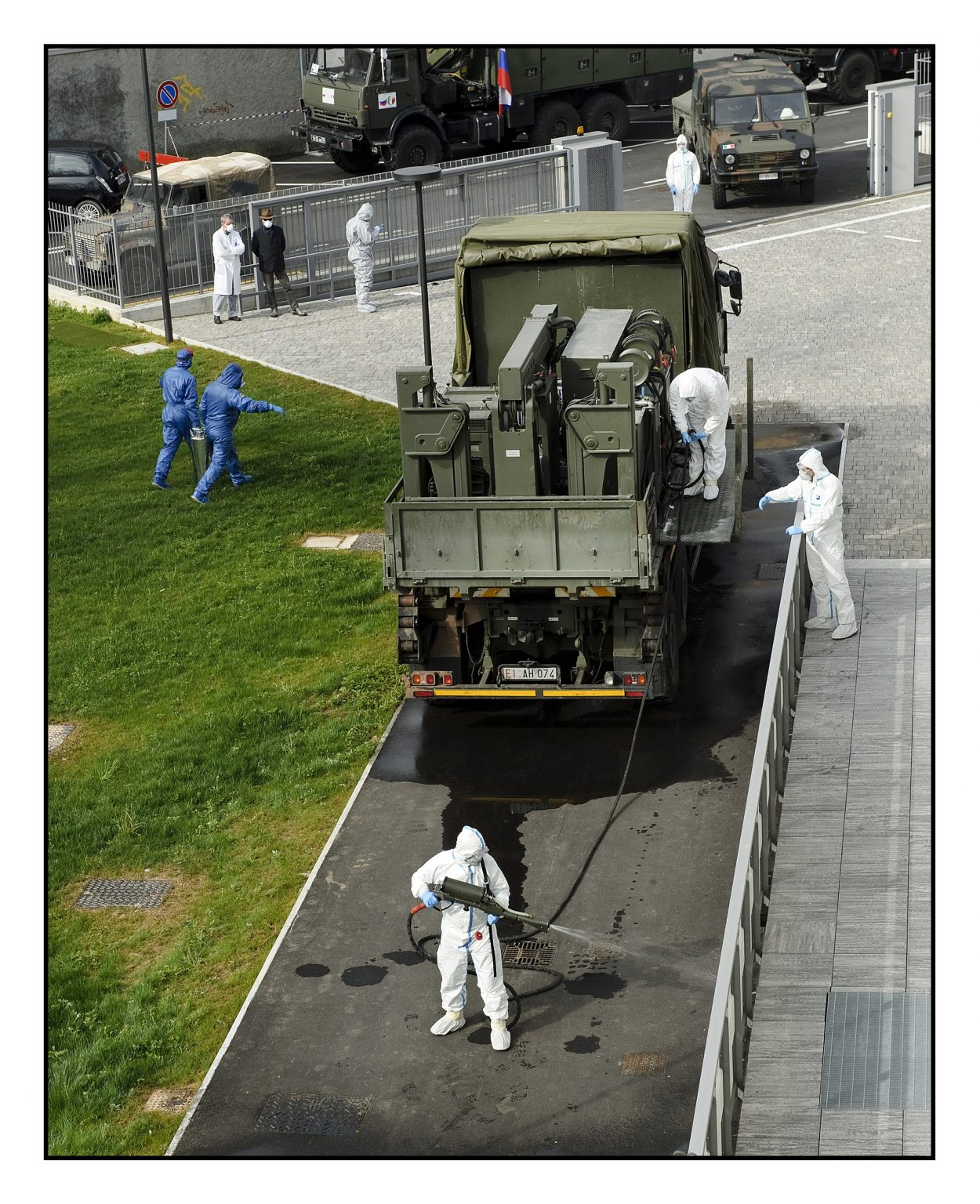 """Sanitation operations in the courtyard of the structure by the soldiers of the Special Chemical, Bacteriological, Radioactive and Nuclear Defense Forces of the Russian army in collaboration with the """"Cremona"""" Biological and Chemical Nuclear Defense Regiment (CBRN) of the Italian army.  Ponte San Pietro, Fondazione Casa di Riposo Onlus, April 1st 2020"""