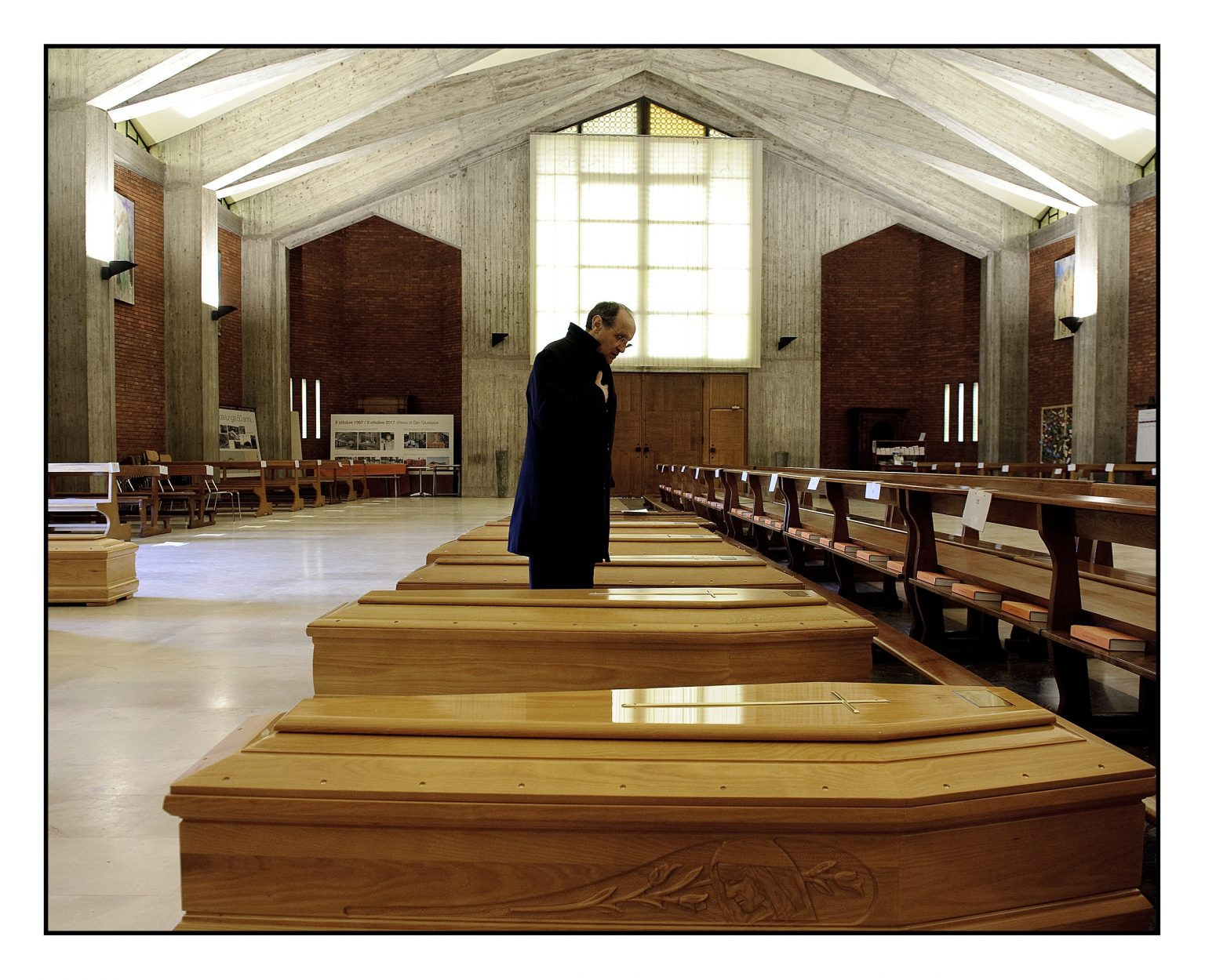 Coffin depots in Bergamo area. Don Mario, priest of San Giuseppe church, says a prayer for the new arrivals. His church in those days becomes an emergency depot where they are stored the coffins arriving from the eastern zones of the Bergamo province. The coffins are therefore sent by military truck transports out of the province, in the crematory ovens of northern Italy as available. Seriate, Bergamo, March 26th 2020