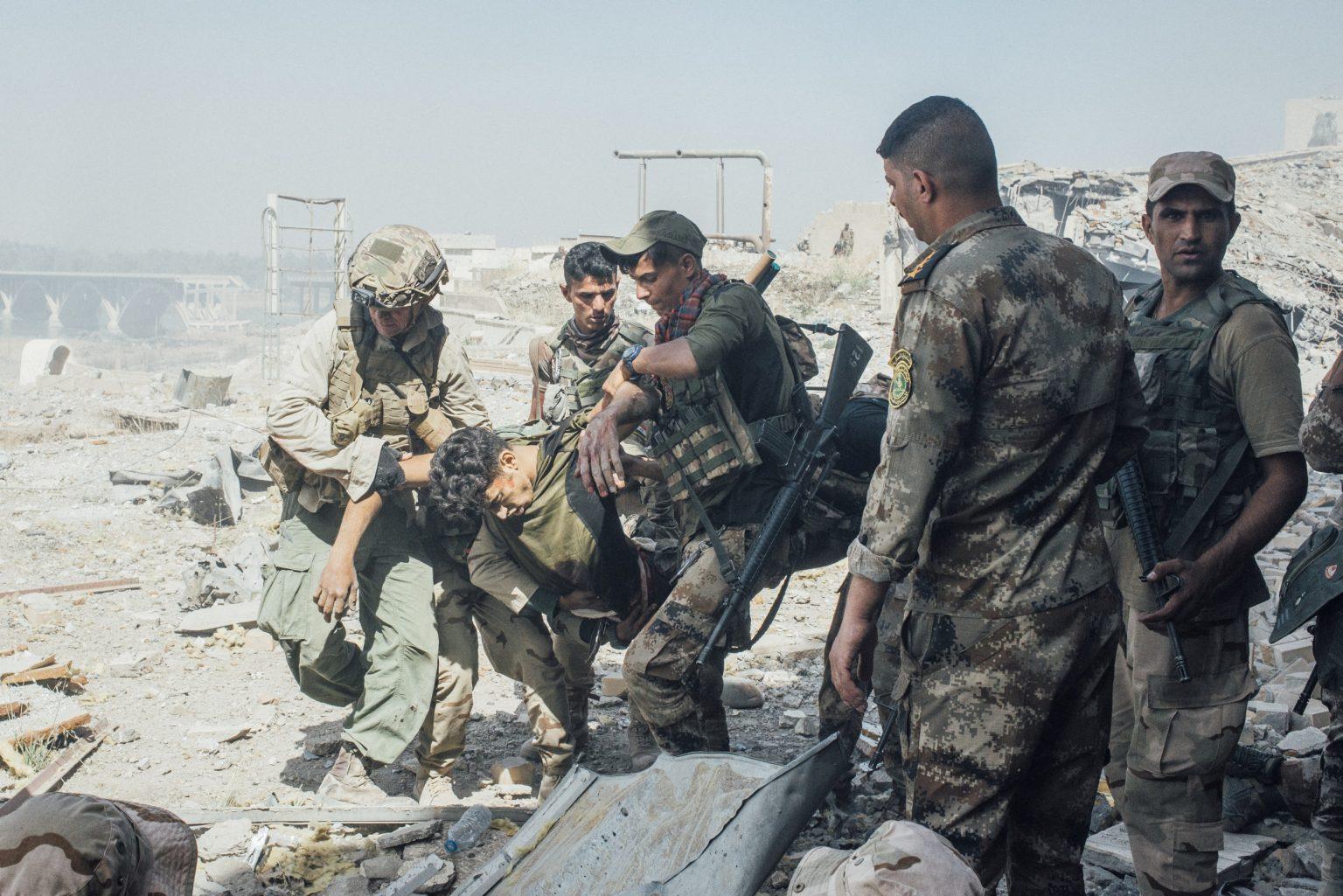 A member of the Iraqi Army hit by an Isis sniper during an attempt to retake Al-Shifa Hospital, is carried away from the front line, in west Mosul. Iraq, 2017  IRAQ. Mosul. Maggio 2017 - Un membro dell'esercito iracheno colpito da un cecchino dell'Isis durante un'operazione per riprendere il controllo dell'ospedale Al-Shifa, nella parte ovest di Mosul.