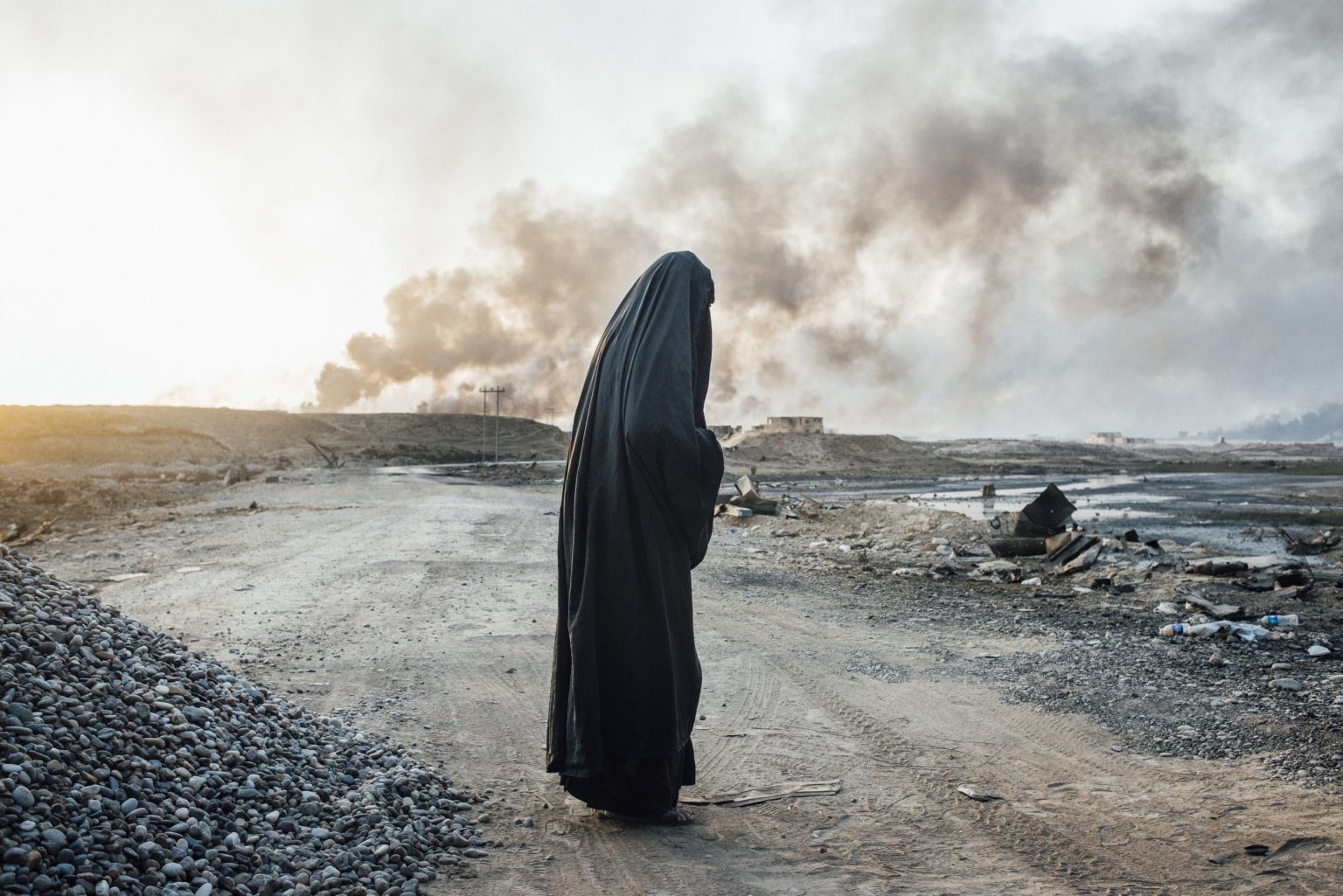 A woman from Shora, a village liberated from Isis by Iraqi army, waits at Qayara checkpoint before being taken to a refugee camp. Mosul, Iraq, 2016