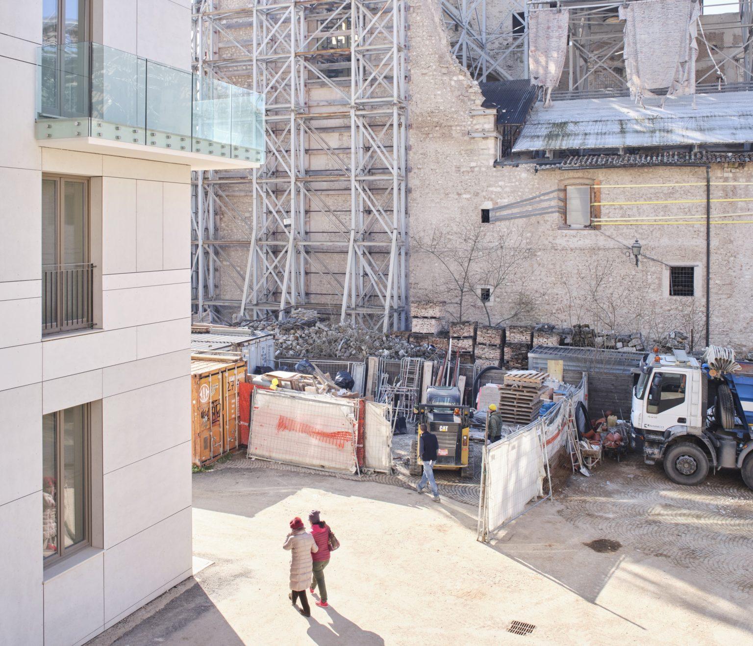 Piazza Santa Maria Paganica: new reinforced concrete building and Church of Santa Maria Paganica, uninhabitable since April 2009. L'Aquila, historic center, Italy, 2019