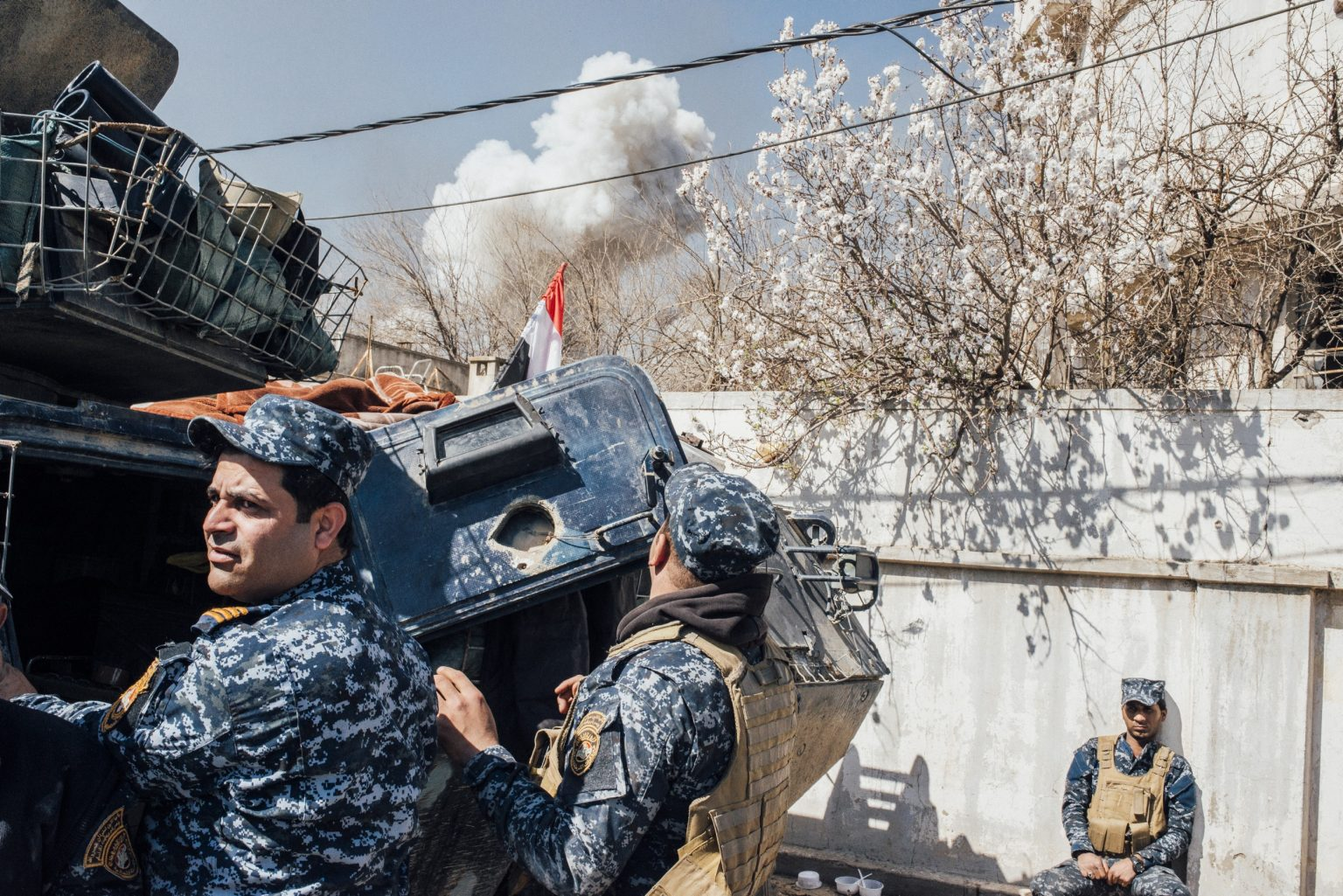 Members of the Federal Police take a shelter after a car bomb explosion, in Southwest Mosul, Iraq, 2017