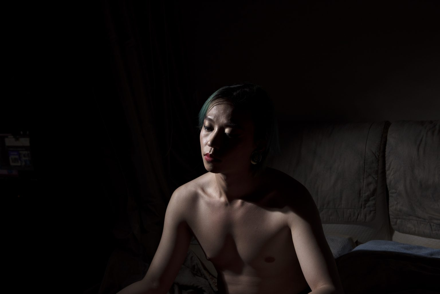 Fei Fain (28) portrayed in his home. He is a professional Drag Queen and a Airbnb host. His parents know about his sexuality but they talk about it. Taipei. Taiwan, 2019