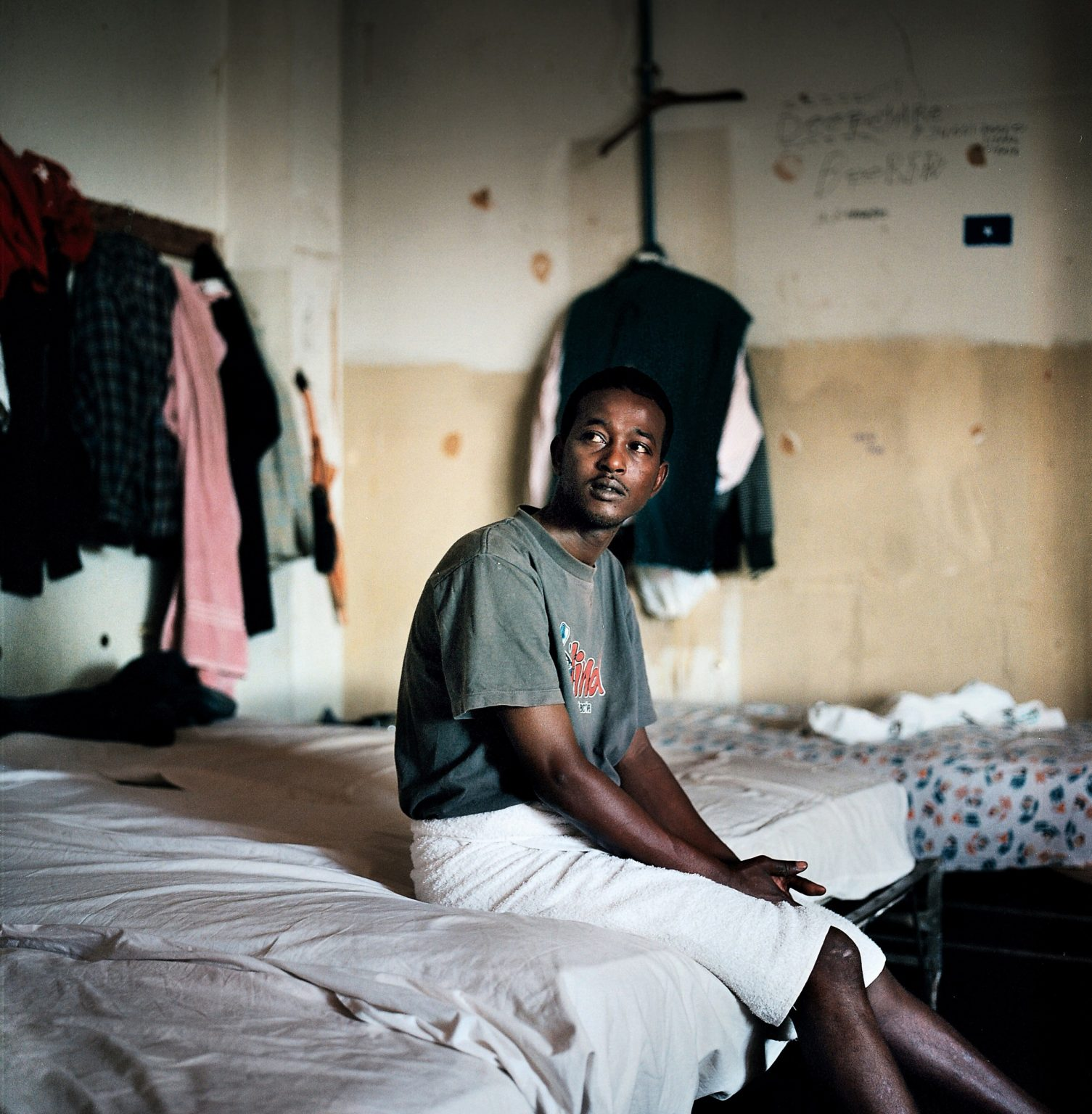 A refugee from Somalia is seen sitting on his bed in a former pediatric hospital located few miles away from the historical centre of the city. The former hospital fell into disuse years ago. It became a temporary shelter to a small community of refugees from Somalia waiting for their political status to be recognized by the Italian authorities.
