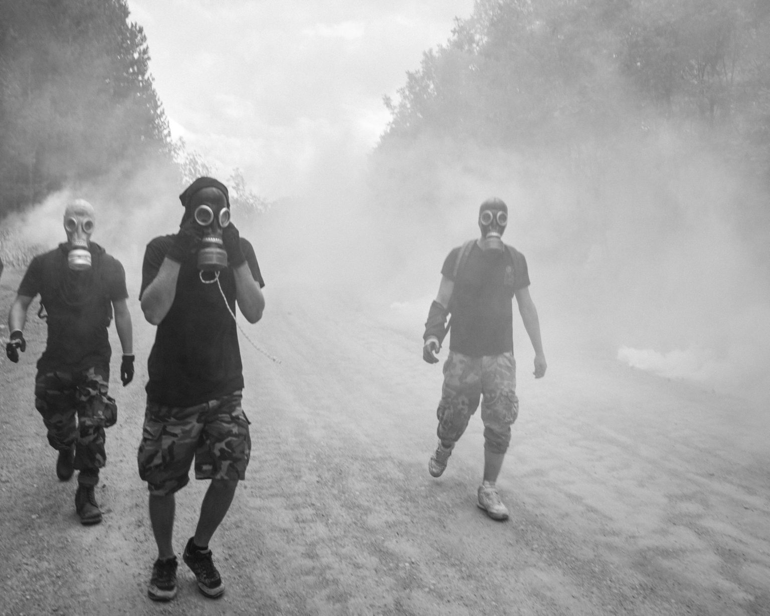 Demonstrators retreating amid the smoke of teargases shot by Ellenic anti riot police at the site where the Canadian company El Dorado started a low cost goldmining project which is endangering the environment of the entire area. Megali Panagia, Greece, 2015