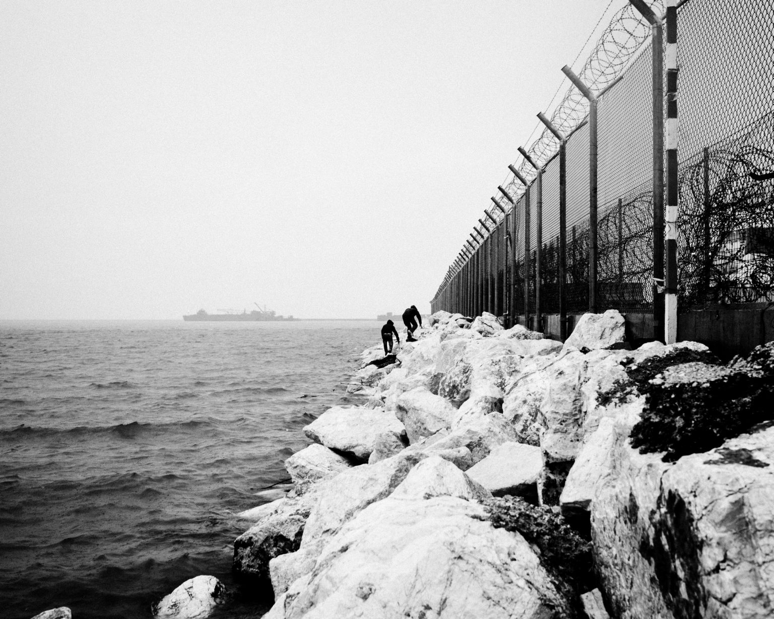 Afghan refugees during an attempt to cross fences dividing them from the embark area of Patra's harbour from where they will try to hide on a ship leaving to Italy. Patra, Greece. 2013