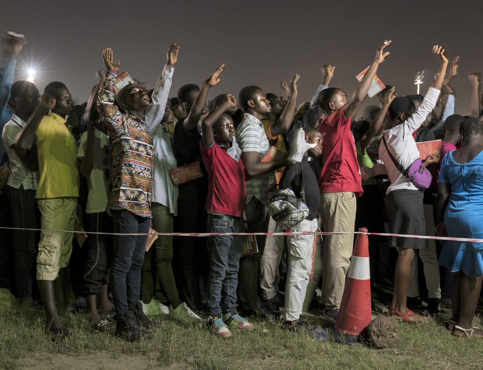 """Young worshipers praying during annual Easter event titled """"Good Friday Miracle Service"""", held in Independence Square by Bishop Dag Heward-Mills. Lighthouse Chapel International (LCI), founded in 1988 by Dag Heward-Mills  is considered to be one of the leading charismatic churches in Ghana, and has over 3000 branches in more than 50 countries. Lighthouse Chapel International is one of the largest of the Pentecostal churches that have appeared since the late 1970s in cities in Africa. Its founder is nowadays considered among the richest pastors in the country. Accra, Republic of Ghana, 2019"""