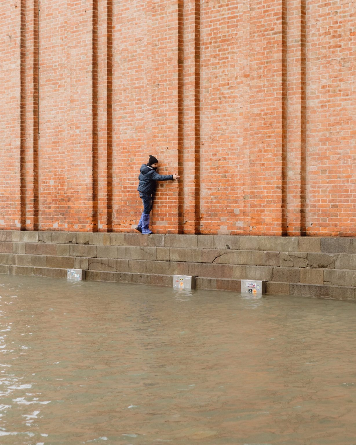 A kid is clinging to the bell tower of St. Mark Square to avoid the water that submerged the city. Exceptional acqua alta, or high water, in Venice, where the tide went up to 187cm, the highest level since the 1966 flood. Brugnaro, the mayor declared a state of disaster. Venice, Italy, 2019