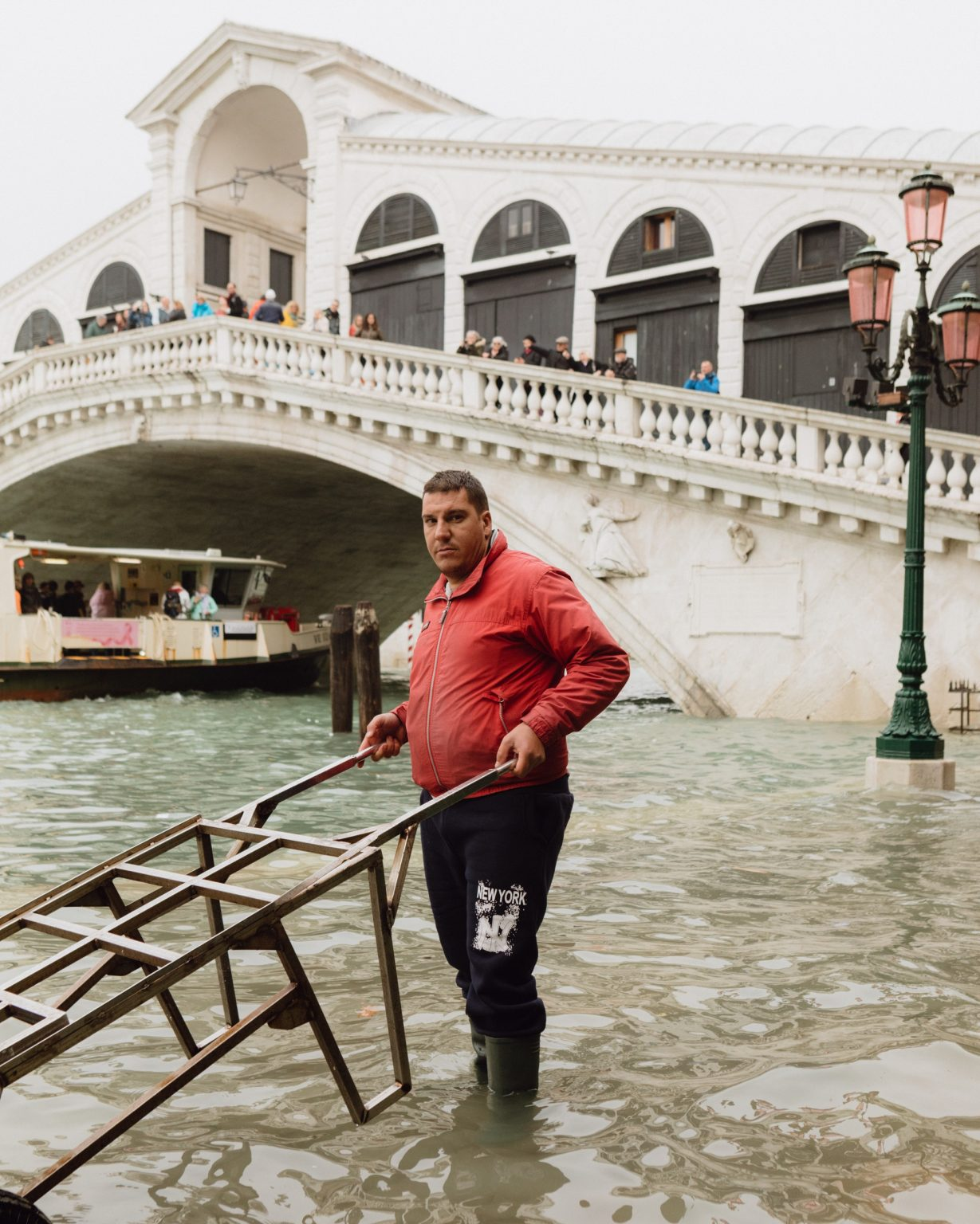 """A man working in front of Rialto Bridge despite the water submerged the area. On the night of the 12th of November 2019, Venice faced one of the most severe flooding of its millennial history. The tide reached 187 centimeters, making it the second highest after the infamous """"Acqua Granda"""" of 1966. Venice, Italy, 2019"""