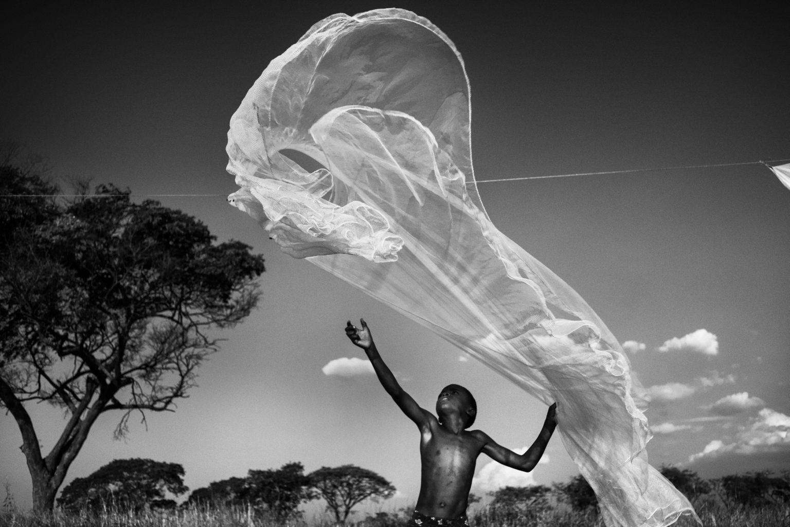 Mthunzi Centre, a socio-educational project and a residential reception centre. Daily activities in the comunity. Joseph hanging the mosquito net to dry.  Lusaka, Zambia, 2019