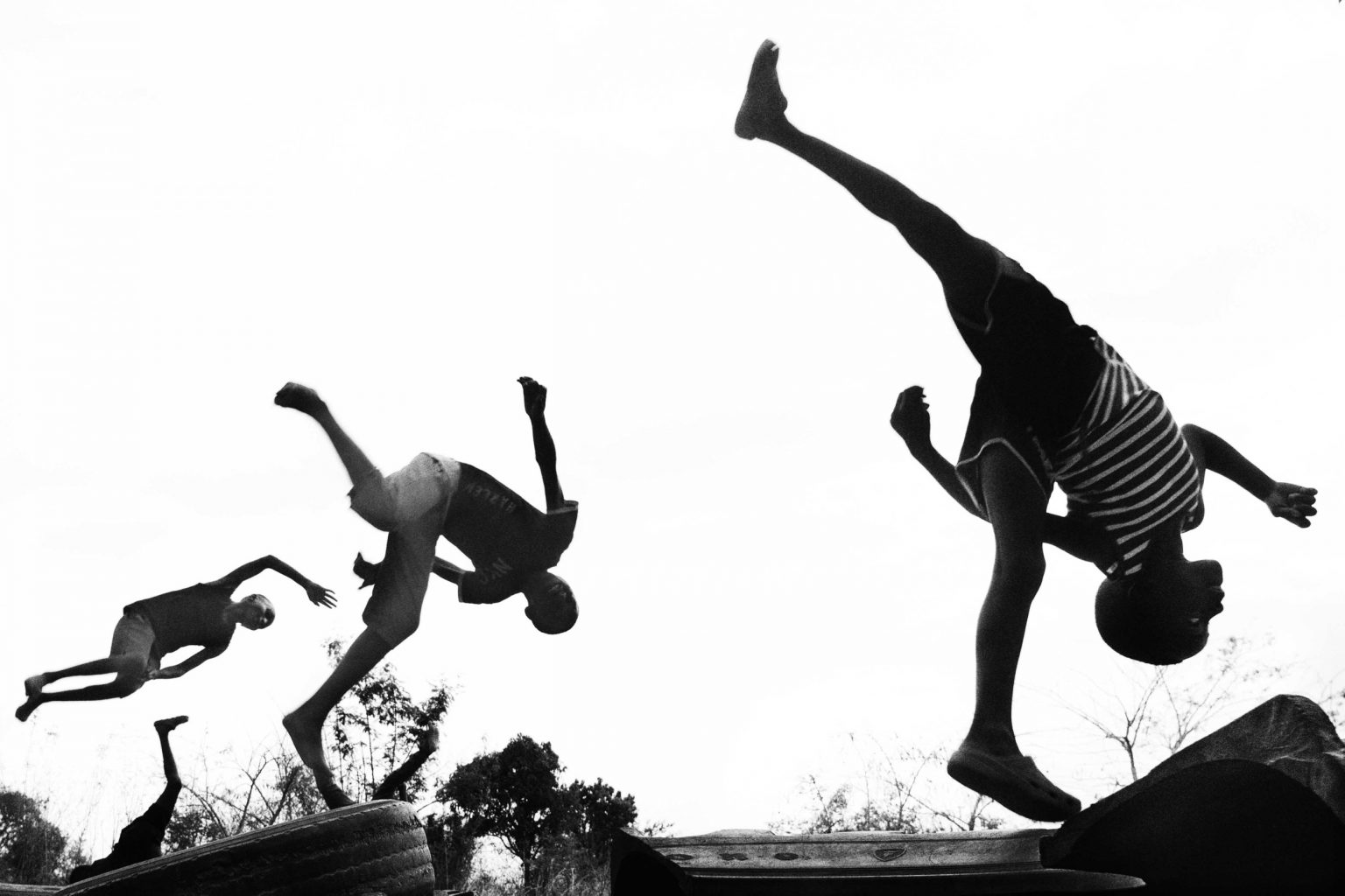 Three boys practice aerial flips using tires as a springboard. Lusaka, Zambia, 2019