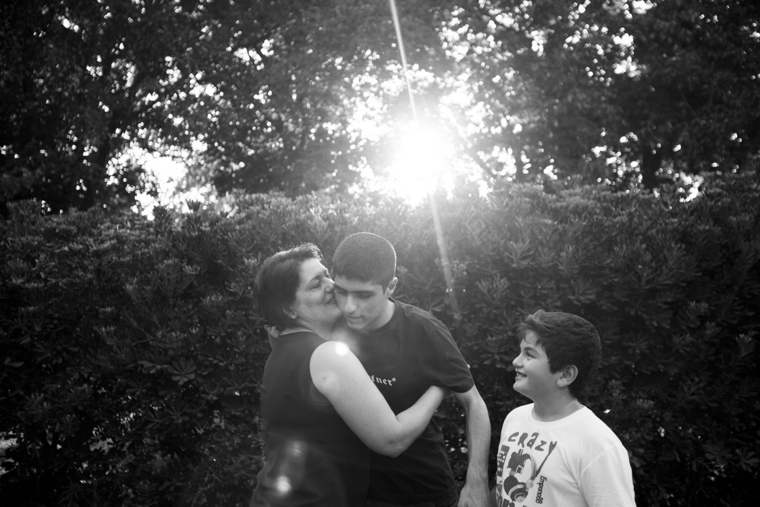 Antonella, the mother of the autistic twins, shares a moment of tenderness with Gennaro. Flavio the third child of the couple looks at them happily. Aversa, Caserta, Italy, 2015