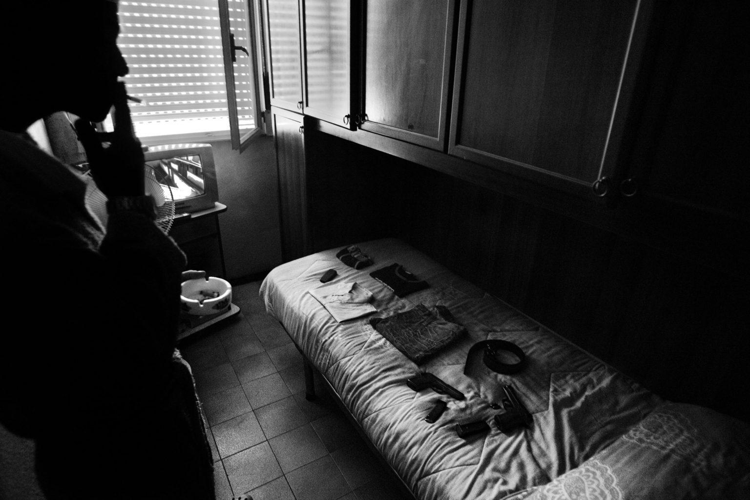 A drug dealer smoking in his room after a shower. Scampia neighborhood. Naples, Italy, 2008   Italia -Napoli, 16/12/2008 - Quartiere Scampia, uno spacciatore che fuma nella sua stanza dopo la doccia.