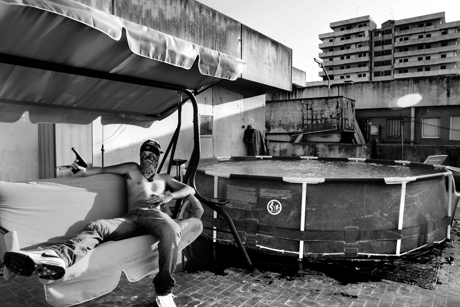 """Portrait of a drug dealer with his gun 7,65 on the top of """"The Sails"""" a particular building so called for their shape. Scampia neighborhood. Naples, Italy, 2009"""