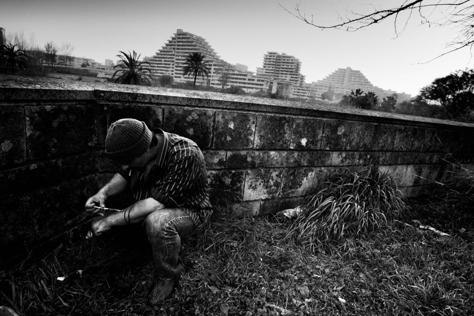Drug addict shooting drugs next to the Sails. Scampia neighborhood. Naples, Italy, 2008