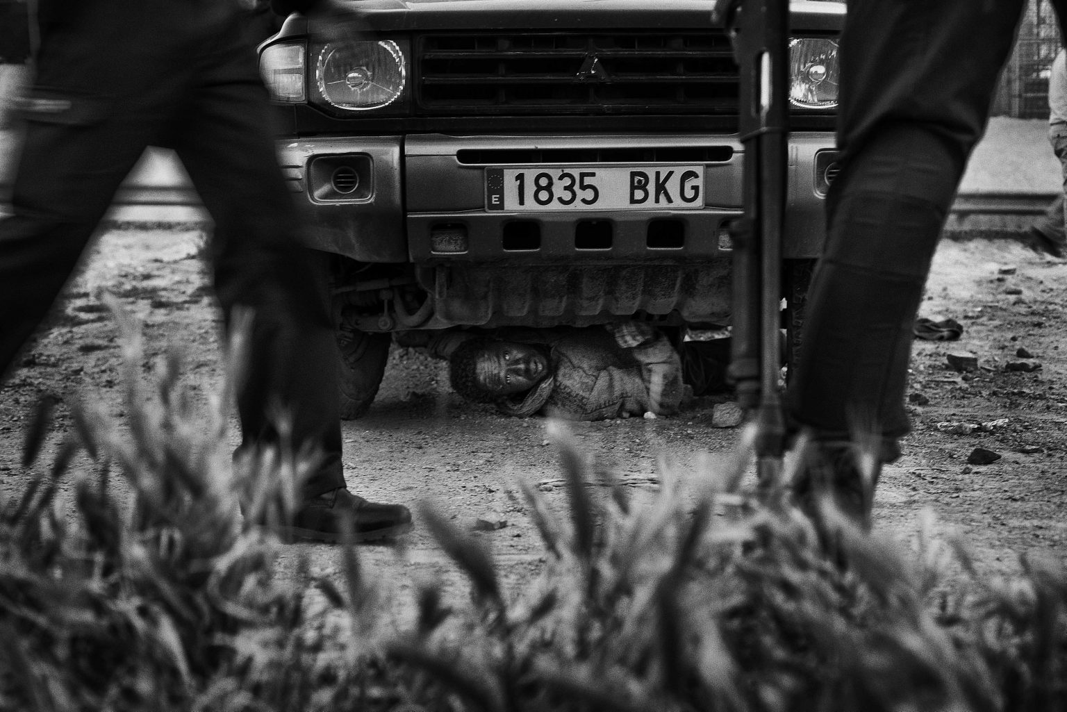 Sub-Saharan migrant hides himself under a vehicle trying to avoid an illegal expatriation by the Guardia Civil. He eventually managed to escape.  Melilla, Spain, 2014