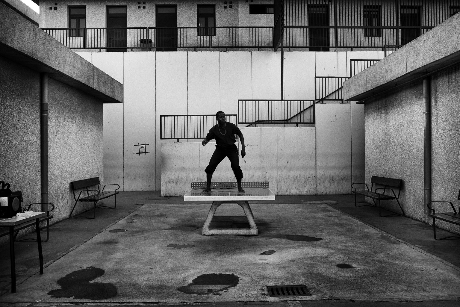 A guest of CETI is dancing on top of a table tennis. African and American hip hop music is constantly played in the courtyard. Ceuta, Spain, 2012