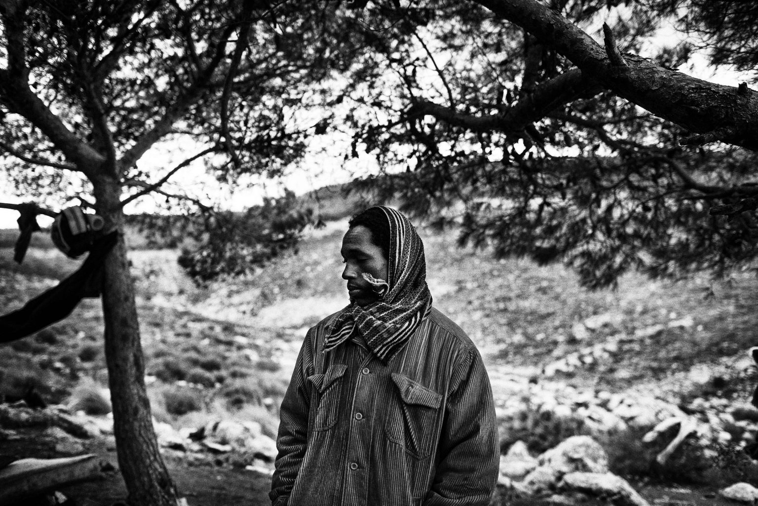 In the forests and on the mountains that surround the city, groups of Sub-Saharan migrants survive and wait for the right moment to cross illegally the border that separates Morocco and the city of Melilla in Spain. The Moroccan Police and Army constantly harass them and during the night made raids through the migrants camp in order to deport them at the border with Algeria. In the picture, a migrant from Guinea Conakri, waiting to have a lunch. Nador, Morocco, 2012