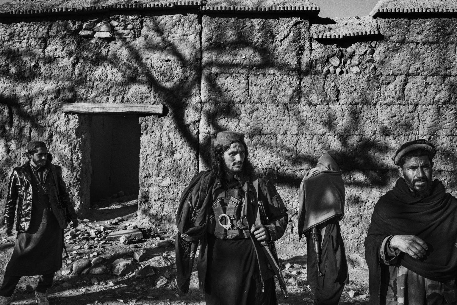 """Nangarhar province, Afghanistan, December 2019 - A group of Taliban fighters gather in the morning in Khogiani district. Abdul Rahman (centre), 20 years old, joined the Taliban 6 years ago. He was a farmer before. He lost a hand trying to defuse a bomb. Some members of his family fought against the soviets occupation. He says he would be glad to return to farming when there will be an islamic government in Afghanistan, but he also add that he will miss jihad because """"this is what feeds you in the after life"""". >< Provincia di Nangarhar, Afhanistan, dicembre 2019 - Un gruppo di combattenti talebani si raduna al mattino nel distretto di Khogiani. Abdul Rahman (al centro), 20 anni, si è unito ai talebani 6 anni fa. Prima era un contadino; ha perso una mano nel tentativo di disinnescare una bomba. Alcuni membri della sua famiglia hanno combattuto contro l'occupazione sovietica. Dice che sarebbe felice di tornare al lavoro agricolo quando ci sarà un governo islamico in Afghanistan, ma aggiunge anche che gli mancherà la jihad perché """"questo è ciò che ti nutre nell'aldilà""""."""