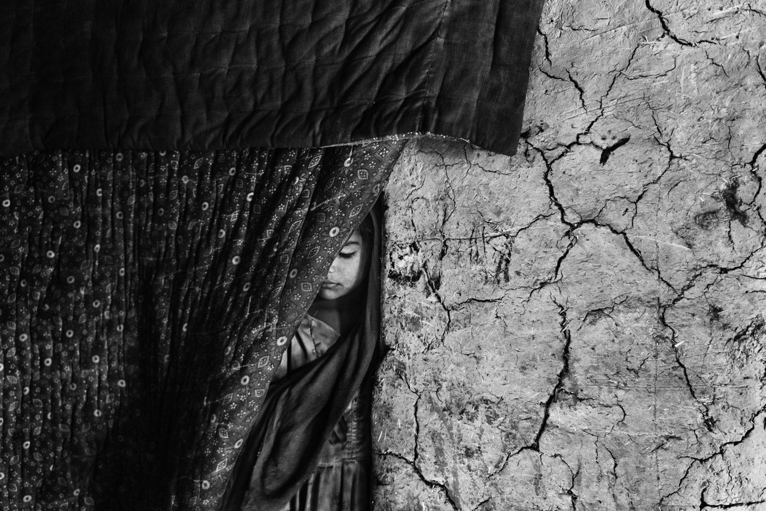 Kabul, Afghanistan, March 2019 - A girl stands at the entrance of her family mud house in Hussain Khail informal settlement, in the outskirts of Kabul. Her uncle and brother were killed in an airstrike that struck the compound were the family lived in the village of Chardara, in the northern province of Kunduz. Survivors were stuck in the crossfire between the Taliban and the Afghan Army for an entire day before they could leave the area. During a break in the fightings  they were evacuated directly to Kabul. Almost two-thirds of the Afghan population lives in areas directly affected by conflict; Aaccording to UNHCR data 340 thousand people were forced to flee from their homes in 2018 setting the total of internal displaced people to a record number of almost 2 million. >< Kabul, Afghanistan, marzo 2019 -  Una bambina all'entrata della casa di fango in cui abita con la famiglia nell'insediamento di Hussain Khail, alla periferia di Kabul. Suo zio e suo fratello sono stati uccisi in un attacco aereo che ha colpito la casa dove viveva con la famiglia nel villaggio di Chardara, nella provincia settentrionale di Kunduz. I sopravvissuti sono rimasti bloccati dai combattimenti a fuoco tra i talebani e l'esercito afghano per un giorno intero prima che potessero lasciare l'area. Durante una pausa dai combattimenti sono stati evacuati direttamente a Kabul.  Quasi due terzi della popolazione afgana vive in aree direttamente colpite dal conflitto; secondo i dati dell'UNHCR, 340mila persone sono state costrette a fuggire dalle proprie case nel 2018, portando il totale degli sfollati interni a un numero record di quasi 2 milioni.