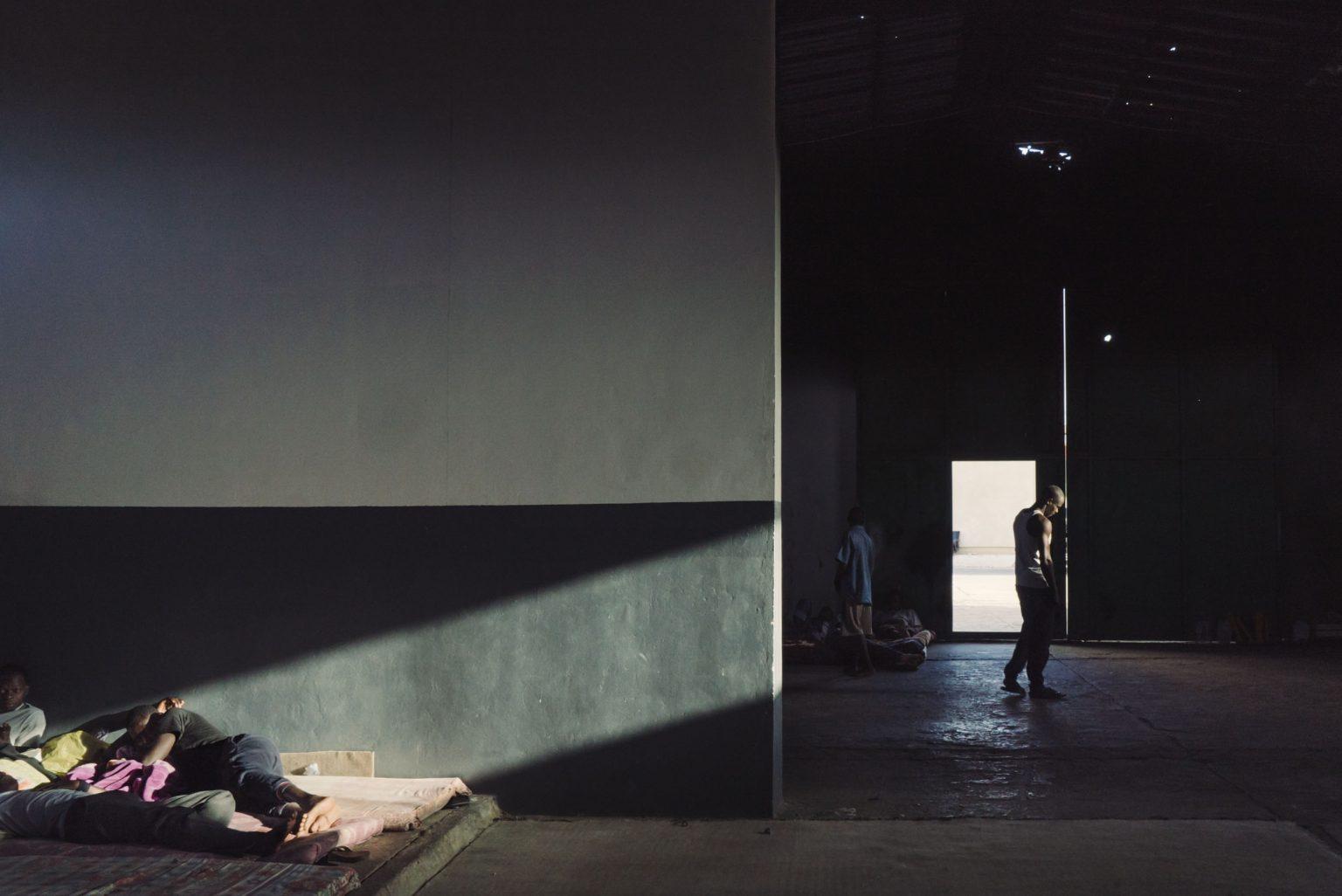 Tripoli, Libya, May 2017 -  An inmate walks in the main cell of the Tadamon detention center. >< Tripoli, Libia, maggio 2017 - Un detenuto nella cella principale del centro di detenzione di Tadamon.