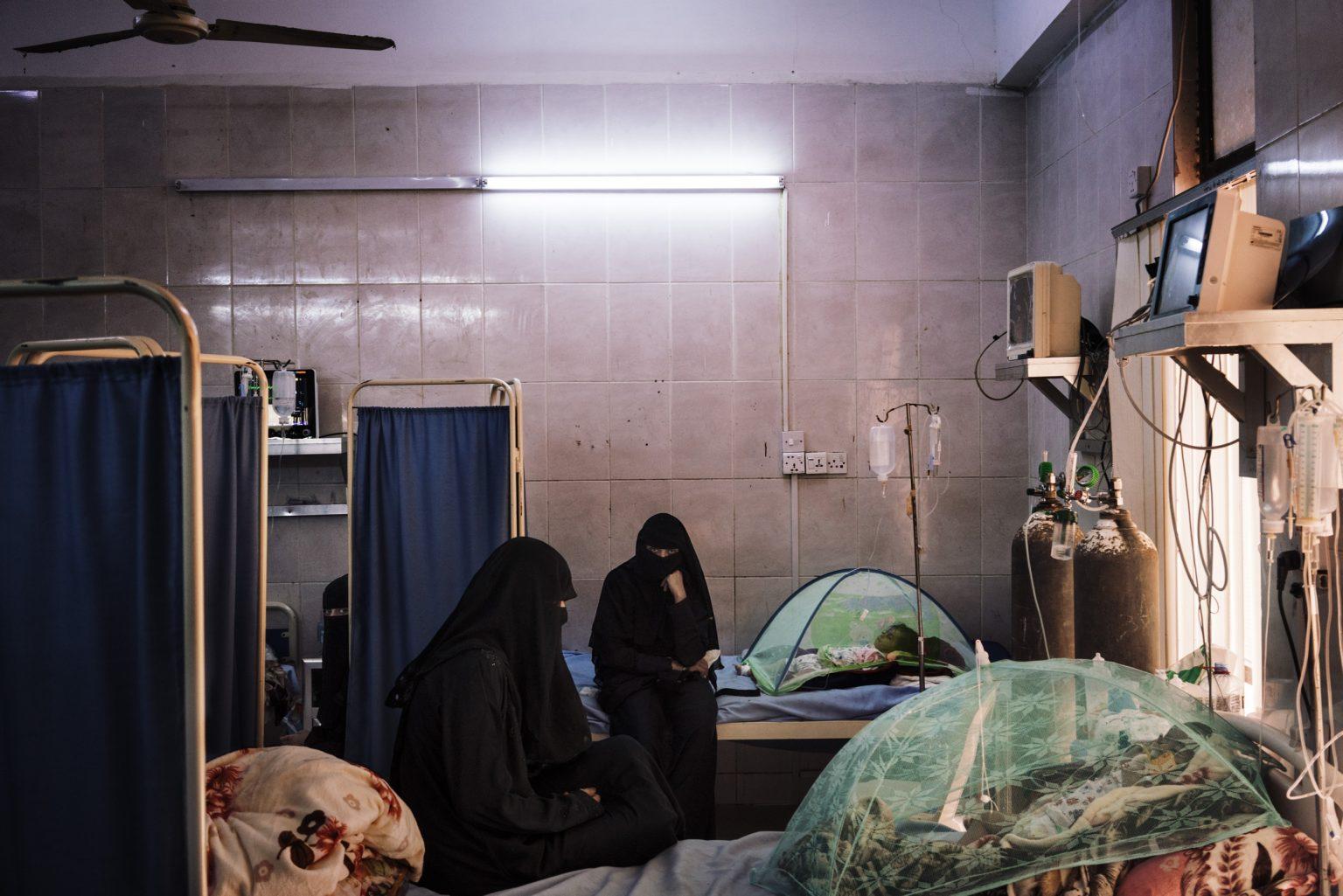 Aden, Yemen, May 21st, 2018 - Women attends their children in the intensive Care Unit of the Sedaqa hospital. There are no doctors in the hospital and discontinuous availability of oxygen and medicines.  A violent confrontation between a member of the militia that control Sedaqa hospital and a doctor on May 14th led to a strike of all the doctors in the hospital. They demand the militia to leave the hospital. The strike created a dangerous situation for many of the patients. Children in the Intensive Care Unit and in the malnutrition wards couldn't see a doctor for days>< Aden, Yemen, 21 maggio 2018 - Alcune donne si prendono cura dei piccoli pazienti nel reparto di terapia intensiva dell'ospedale Sadaqa di Aden. Nell'ospedale non ci sono dottori al momento e la disponibilità di ossigeno e medicine è discontinua. Un violento scontro tra un membro della milizia che controlla l'ospedale Sedaqa e un medico il 14 maggio ha portato allo sciopero di tutti i medici dell'ospedale. Gli scioperanti pretendono che la milizia venga allontanata dall'ospedale. Lo sciopero ha peggiorato la situazione già tragica per molti dei pazienti. I bambini nell'unità di terapia intensiva e nei reparti di malnutrizione non sono stati visitati dai medici da giorni. Lorenzo Tugnoli / The Washington Post / Contrasto