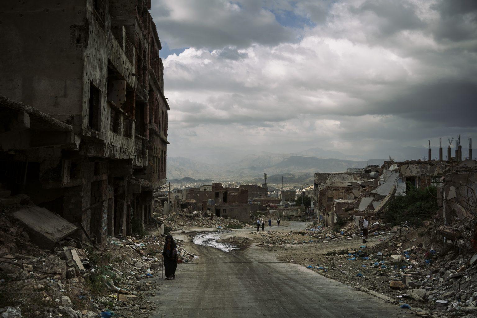 *** SPECIAL   FEE   APPLIES ***Taiz, Yemen, November 2018 - A veiled woman walks near a bombed building in the al-Jahmaliya area. Buildings here have been reduced to rubble, first during fighting between Houthi rebels and local militias struggling to retake the city, then in recent clashes between them. >< Taiz, Yemen, novembre 2018 - Una donna velata cammina vicino a un edificio bombardato nella zona di al-Jahmaliya. Qui gli edifici sono stati ridotti in macerie, prima nei combattimenti tra ribelli Houthi e milizie locali che lottavano per riconquistare la cittàˆ, poi, recentemente, durante scontri tra le stesse.