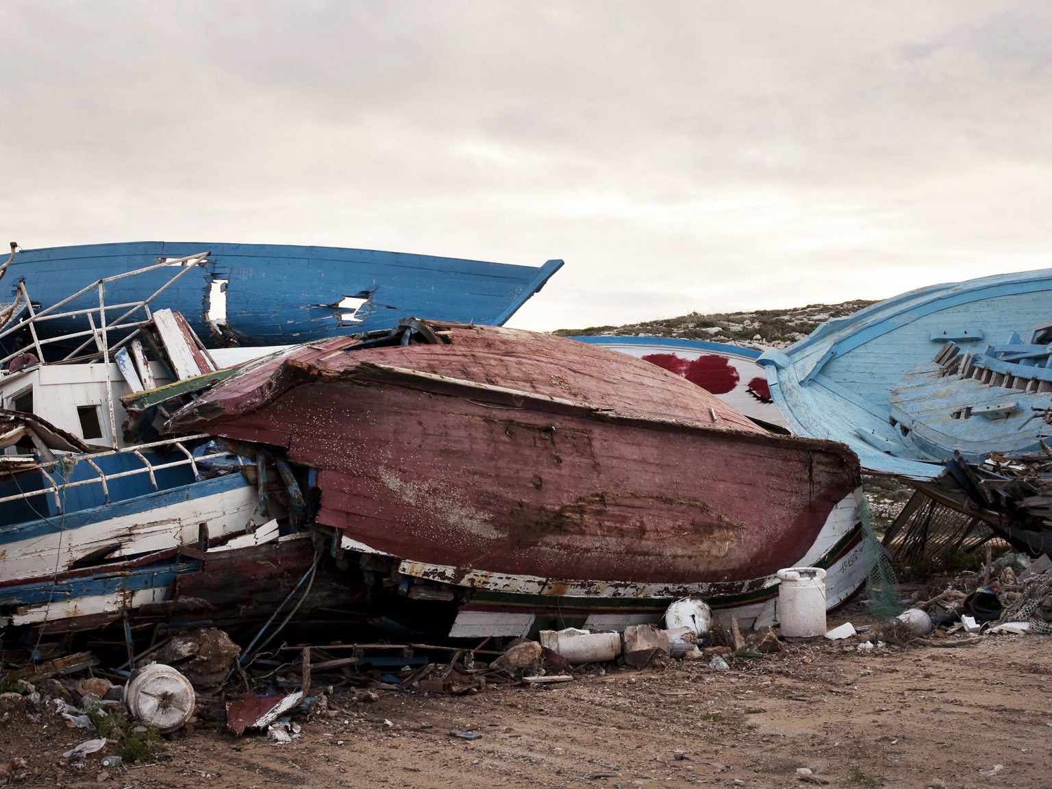 """A view of the so called """"boat cemetery"""", a landfill where boat utilized by migrants to reach Lampedusa used to be stocked. A recent malicious fire had destroyed most of the boats, which are now being stocked in a military area of the island."""