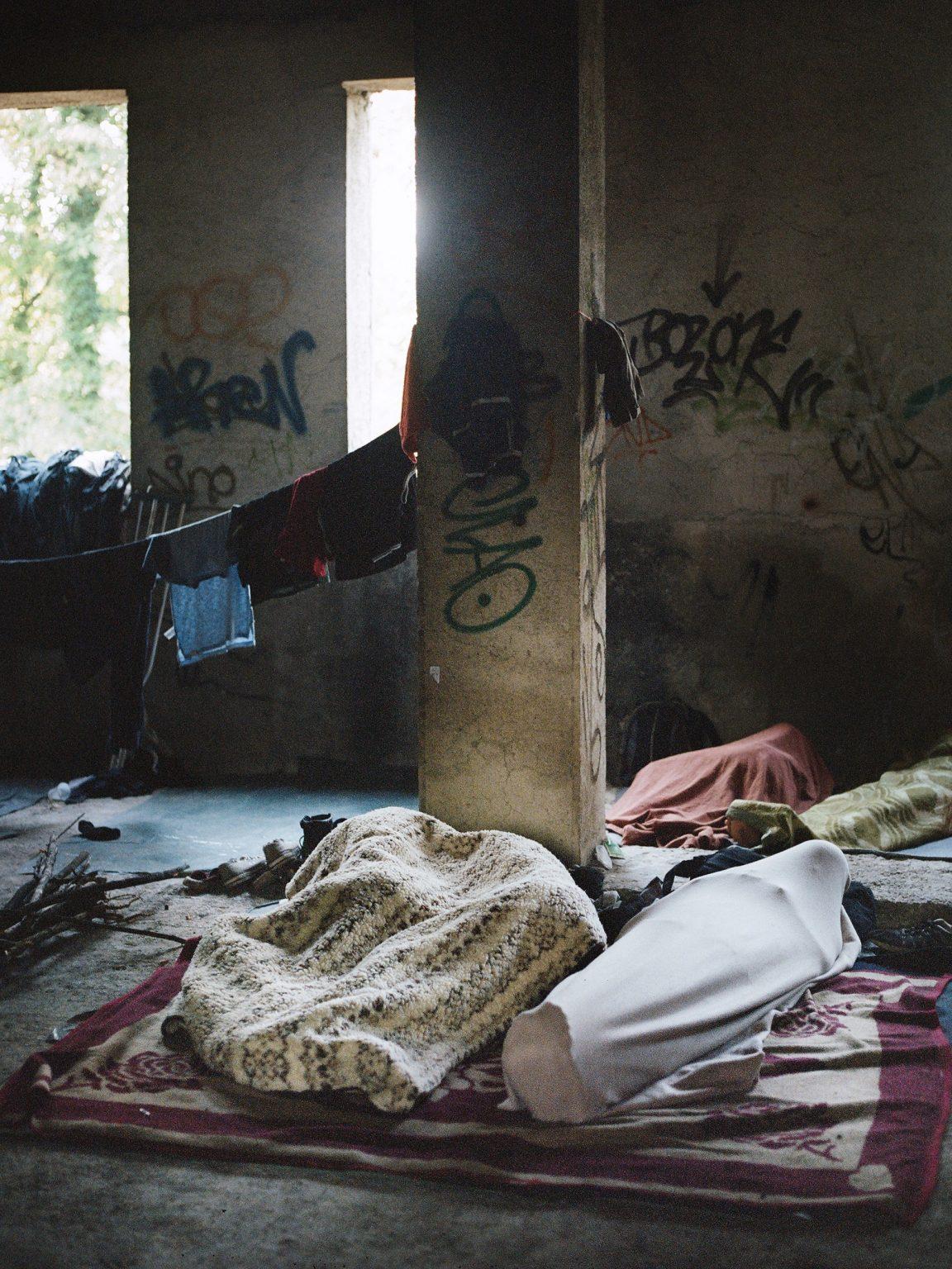 Bihac, Bosnia-Erzegovina. 22 agosto 2018. Alcuni rifugiati dormono in un edificio abbandonato della città. Bihac è divenuta una dei principali punti di passaggio della nuova rotta balcanica, percorsa dai rifugiatio che tentano di entrare in Croazia ed Europa. La popolazione locale non vede di buon occhio l'arrivo di migliaia di rifugiati nella loro piccola città di confine.  Bihac, Bosnia and Herzegovina. August 22, 2018. Some refugees sleep in an abandoned building in the city. Bihac has become one of the main crossing points of the new Balkan route, traveled by refugees trying to enter Croatia and Europe. The local population is frowning upon the arrival of thousands of refugees in their small border town.