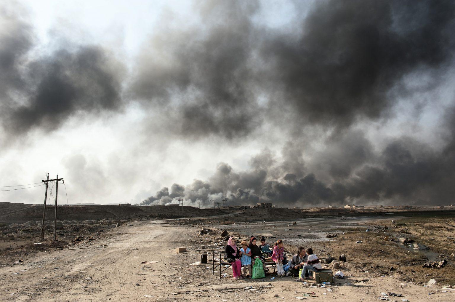 Qayyarah, Iraq, October 27th, ?2016 - Civilians evacuated from the city of Mosul during the operation carried out by the Iraqi army against the so-called Islamic State, which declared the second largest city of Iraq the capital of the Caliphate since 2014. In the picture, an Iraqi family waiting at the checkpoint of the town of Qayyara to be transported to one of the several refugee camps for internally displaced persons.  In the background, piles of smoke of burned oil of the pipelines present in the town, that the so-called Islamic State set on fire ?before to retreat from the area. ----------------- Qayyarah, Iraq, 27 ottobre 2016 - Civili evacuati dalla città di Mosul durante l'operazione condotta dall'esercito iracheno contro il cosiddetto Stato islamico, che dal 2014 ha dichiarato la seconda città dell'Iraq capitale del Califfato. Nella foto, una famiglia irachena in attesa al posto di blocco della città di Qayyara per essere trasportata in uno dei numerosi campi profughi per sfollati interni. Sullo sfondo, fumo di petrolio bruciato degli oleodotti presenti nella cittadina, che il cosiddetto Stato Islamico ha incendiato prima di ritirarsi dalla zona.