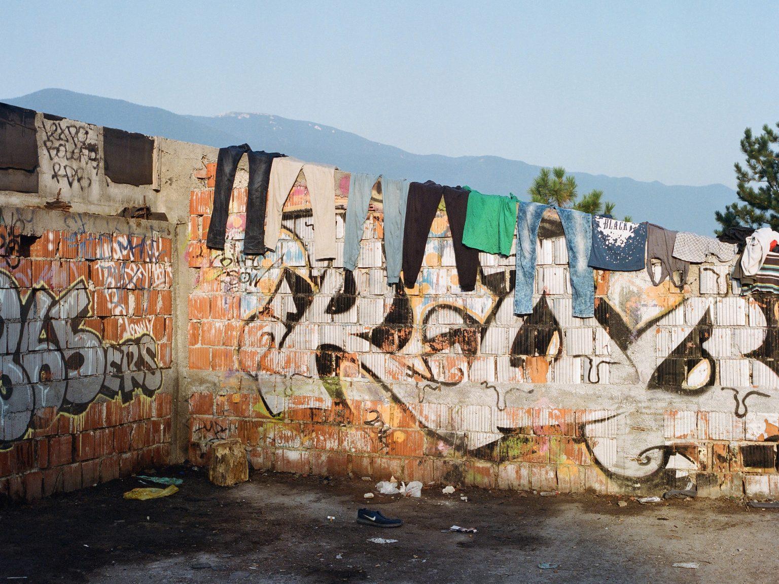 Bihac, Bosnia-Erzegovina. 19 agosto 2018. Alcuni vestiti sono stesi sul tetto di un dormitorio abbandonato, oggi utilizzato come ricovero temporaneo da circa 700 migranti. Gli aiuti umanitari non sono in grado di far fronte al flusso costante di migranti in arrivo nelle zone settentrionali della Bosnia-Erzegovina, offrendo alloggio e vitto solo a un numero esiguo di persone.  Bihac, Bosnia-Herzegovina. 19 August 2018. Clothes drying on the roof of an abandoned dormitory now used as temporary shelter by about 700 migrants. Humanitarian aid is unable to cope with the constant flux of migrants arriving in the northern areas of Bosnia-Herzegovina, offering accommodation and meals only to a small number of people.