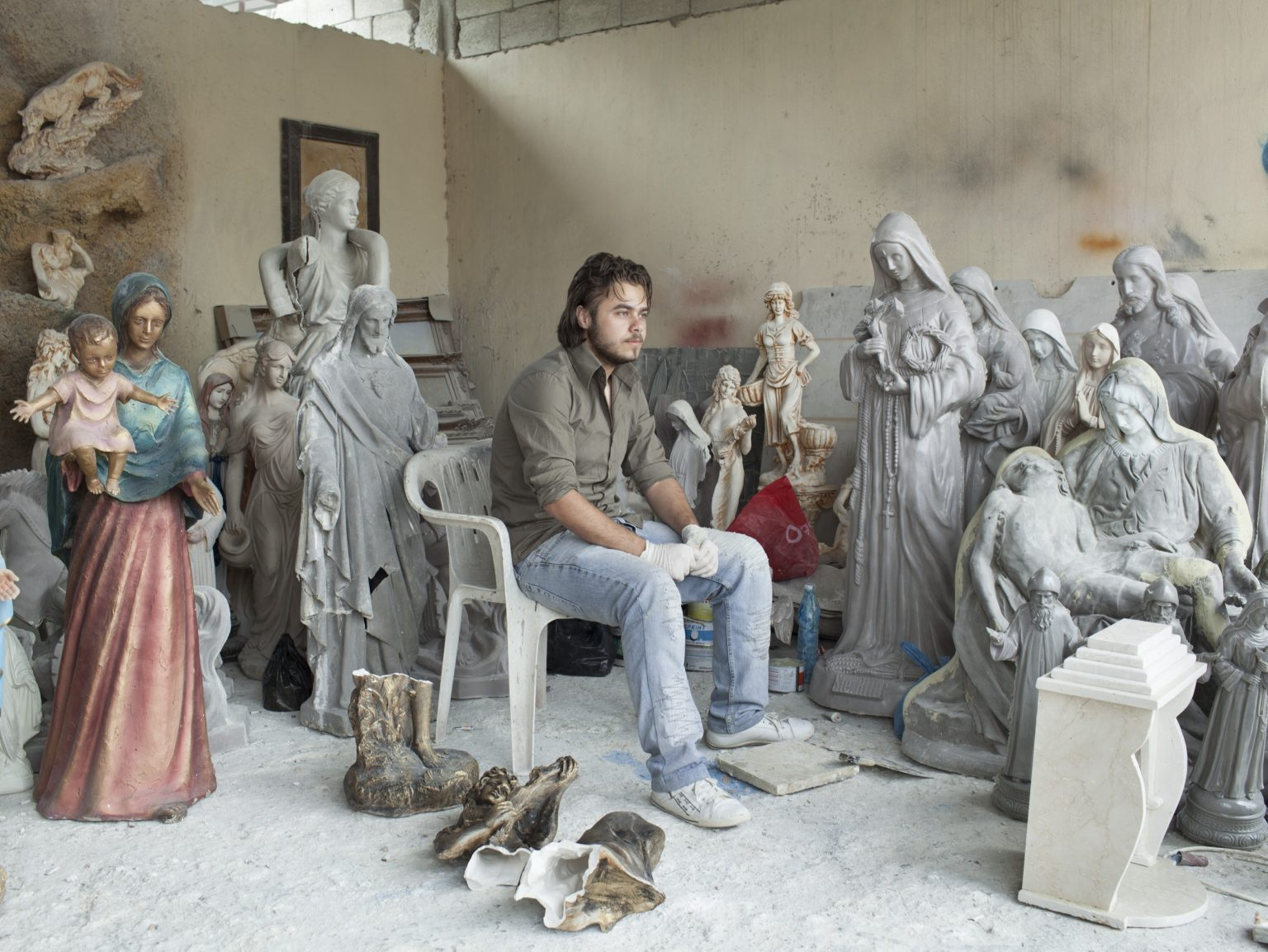 A Christian Syrian refugee is working in a relogous statue shop in Chikka, on the way to Kadisha Valley.