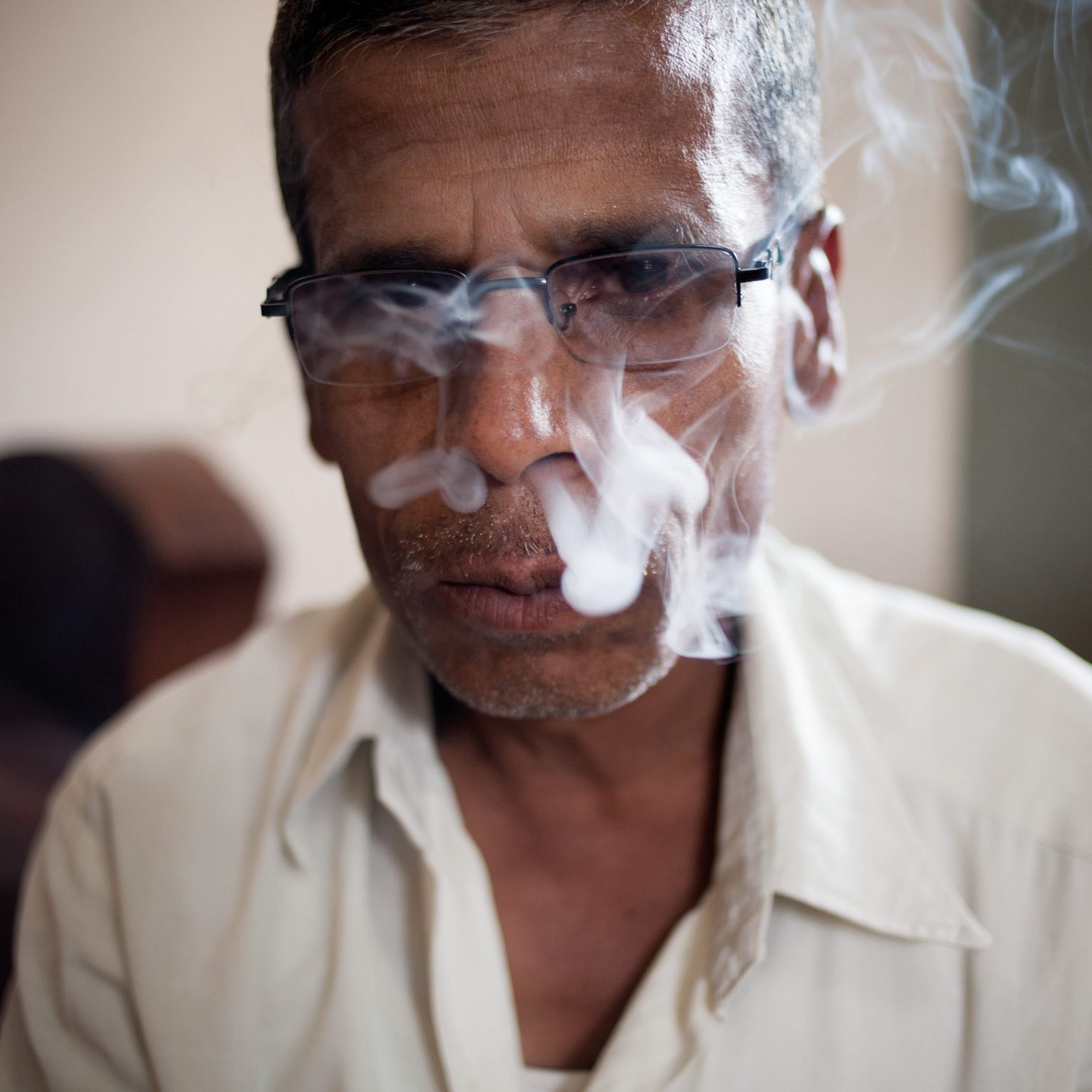 Nipani, India. A bidi tobacco taster expert employed by Shah Chhanganlal Ugarchand, one of the largest tobacco commission agents of the region. A tobacco taster smokes up to 100 bidis/day to grade the different batches of tobacco before sales.
