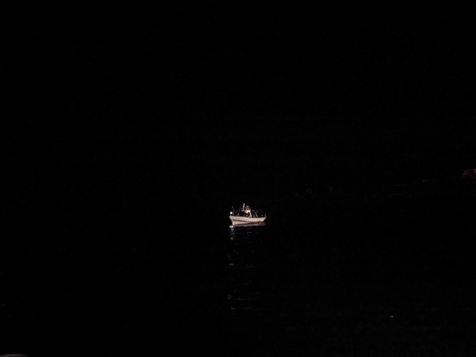 A boat full of migrants from Tunisia is approaching Lampedusa late at night.