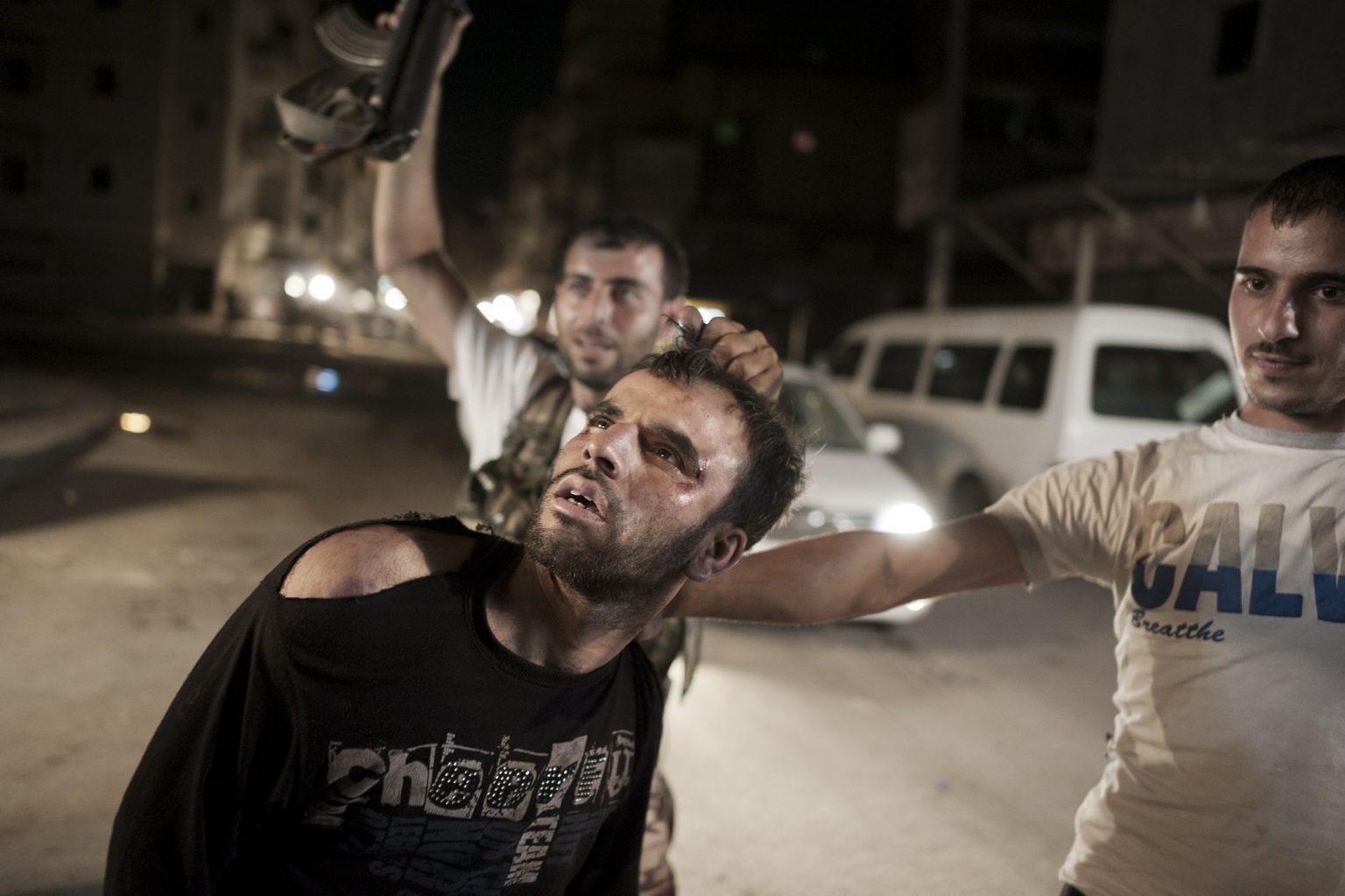Aleppo, September September 25th 2012 - Two r?ebels holding a man accused of? being a spy for the regime. ------------- Aleppo, settembre 2012 - Co?mbattenti dell'Esercito sirian?o libero trattengono un uomo a?ccusato di essere una spia del? regime.