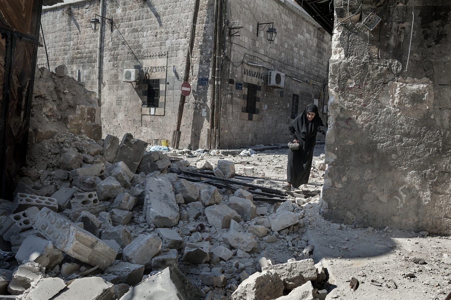 Aleppo, Syria September 24, 2012 - An elderly woman crosses a road destroyed by government bombings. --------------- Aleppo, Siria 24 settembre 2012 - Un'anziana donna attraversa una strada distrutta dai bombardamenti governativi.