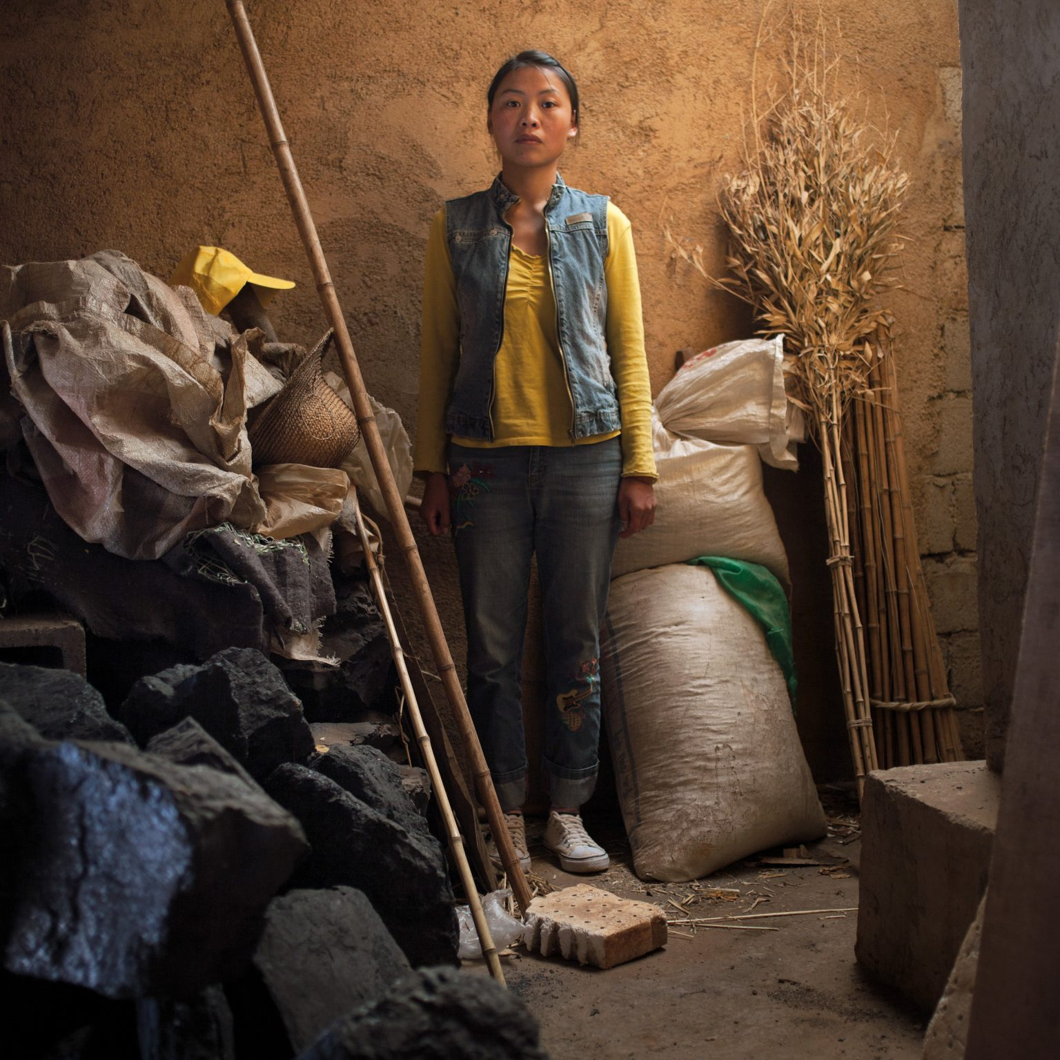 Xundian, China. Wang Zhi Hui, a tobacco grower, in her family barn. Xundian is one of poorest rural areas in Yunnan Province. Land is hilly and the soil infertile. Some 180 people reside in this village and almost all of them grow tobacco. The tobacco industry has been largely responsible for the economic growth of the province but it has failed to spread the wealth to the rural area where around 87 percent of the province's population live. Out of a total population of 41 million, about 6 million people in the province still live below the national poverty level at an annual income below USD 70 . A tobacco grower in Yunnan earns an average of USD 148 per Mu (1 Mu = 666 Square meters) compared with a vegetable farmer who earns an average of USD 595 per Mu. In China, about 1 million hectares of land are utilized to grow tobacco, 40% of which are in Yunnan.