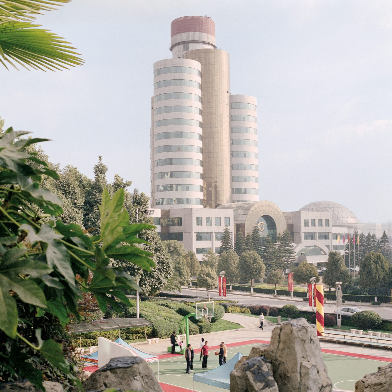"""Kunming, China. The headquarters of the Kunming Tobacco factory. Benefits and corporate welfare for company workers are such that a job in Honghe is regarded as very prestigious.   The factory belongs to Honghe Tobacco Company, part of the Honyun Honghe Group. With the production of 230 billion cigarettes per year, the group represents the world's fourth-largest producer after Philip Morris International Inc., British American Tobacco PLC and Japan Tobacco Inc. in terms of production volume and annual revenues of more than USD 6 billion. The group is the result of the recent merging of two companies, and possesses production facilities in Yunnan and the northwestern Xinjiang region.  China's State Tobacco Monopoly Administration is encouraging tobacco companies to merge and benefit from economy of scale. The industry's umbrella state-owned monopoly company, China National Tobacco Corp., is planning to form 10 major tobacco companies throughout the country through mergers.  Honghe controls 60% of Yunnan's cigarette market. An anonymous informant interviewed by the Author affirms that the company recently introduced Jia Zi and Win (""""Kiss"""") to attract more female consumers. The percentage of male smokers in China is beginning to decrease from a high of about 60%, while the percentage of female smokers remains, for now, very low."""