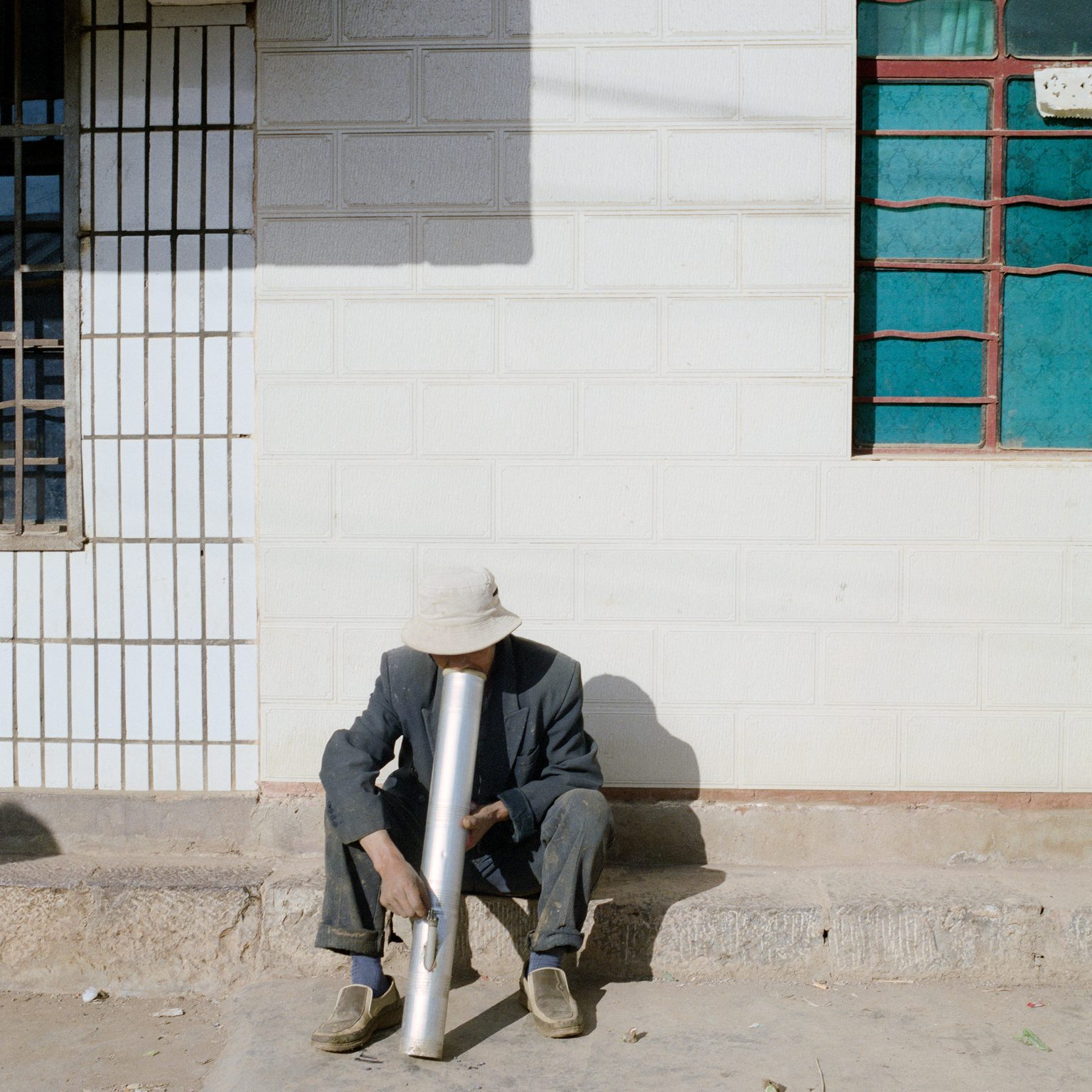 Yuxi, China. A man smoking from a local water pipe. Tobacco is commonly cultivated in the province and some of the tobacco is kept and used by the farmers.