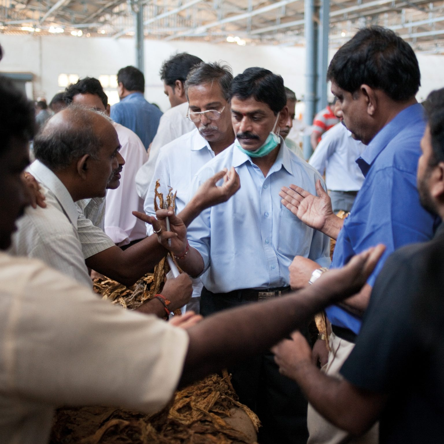 Periyapatna, India. P. Jayarama (centre), auction superintendent of the Tobacco Board auction floor, accepts bids for the exhibited tobacco bales. Tobacco prices range between USD 1-3 per kilo.