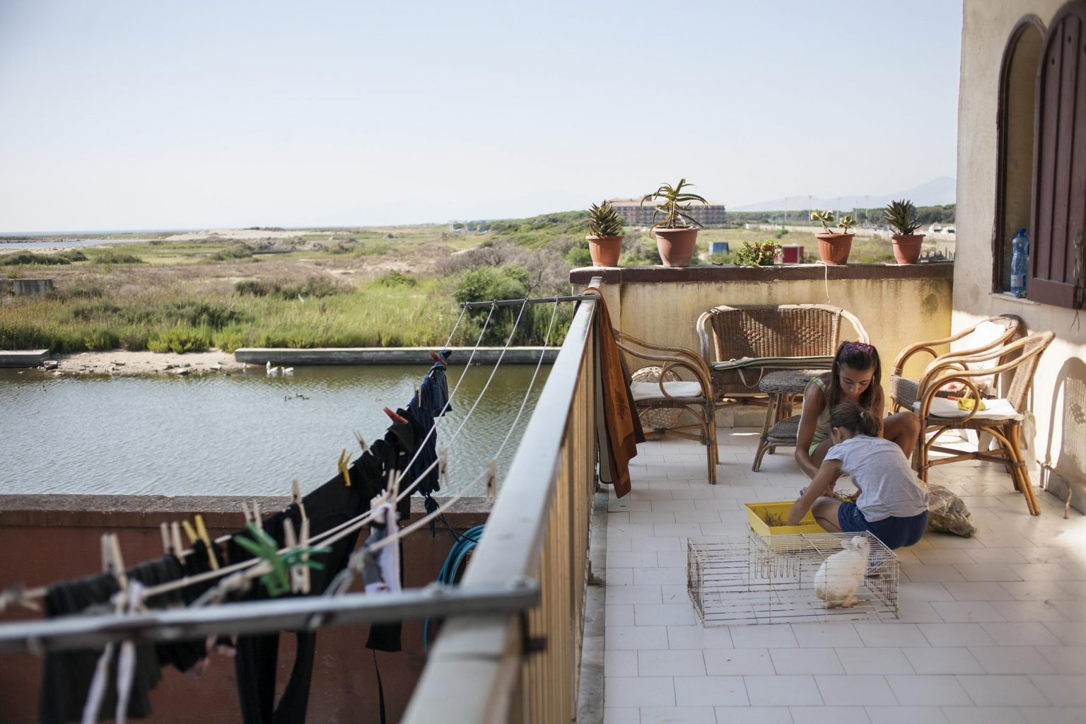 Alessandra and Federica are on their house terrace cleaning the rabbit's cage.