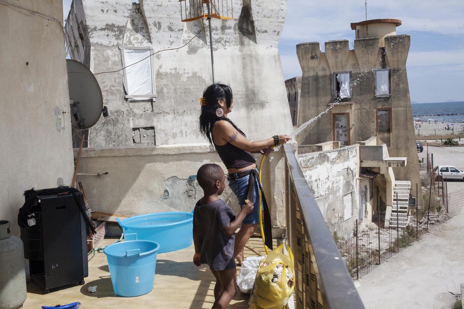 Claudia plays with a water pipe from the balcony of a friend's apartment in Parco Saraceno.  Claudia gioca con un tubo d'acqua dal balcone dell' appartamento di un'amica al Parco Saraceno.