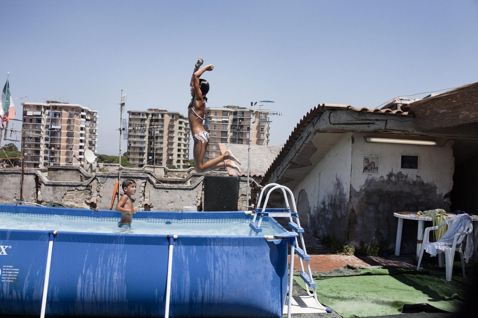 Federica, Claudia's youngest daughter is seen jumping in a prefabricated swimming pool, owned by another abusive habitant of the Saraceno park,presently at house arrest for robbery.