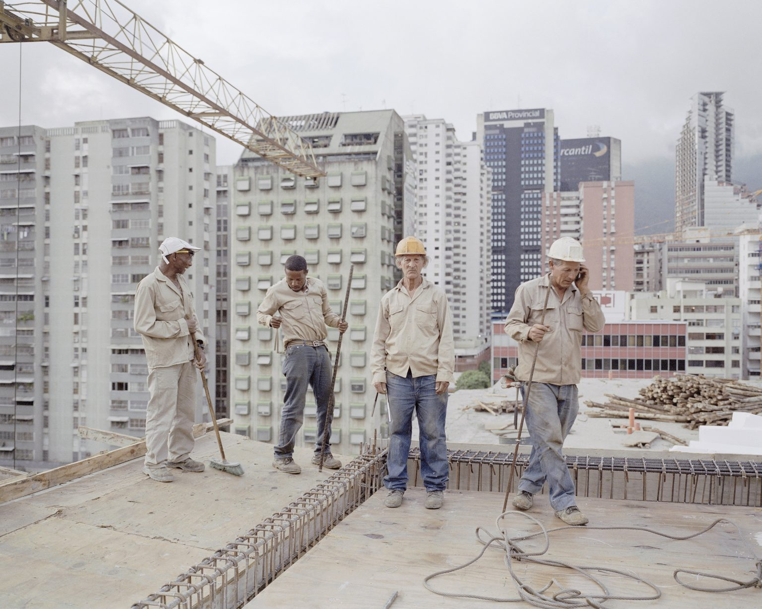"""Some workers on the roof of a contruction site in Caracas. The building is part of the program """"Mission Vivienda"""" to give houses to the poorest part of the population."""