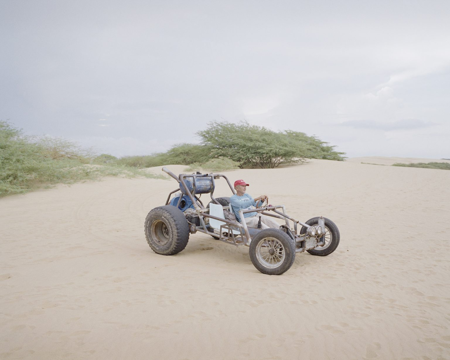 A man with his selfmade car in the desert of Coro.