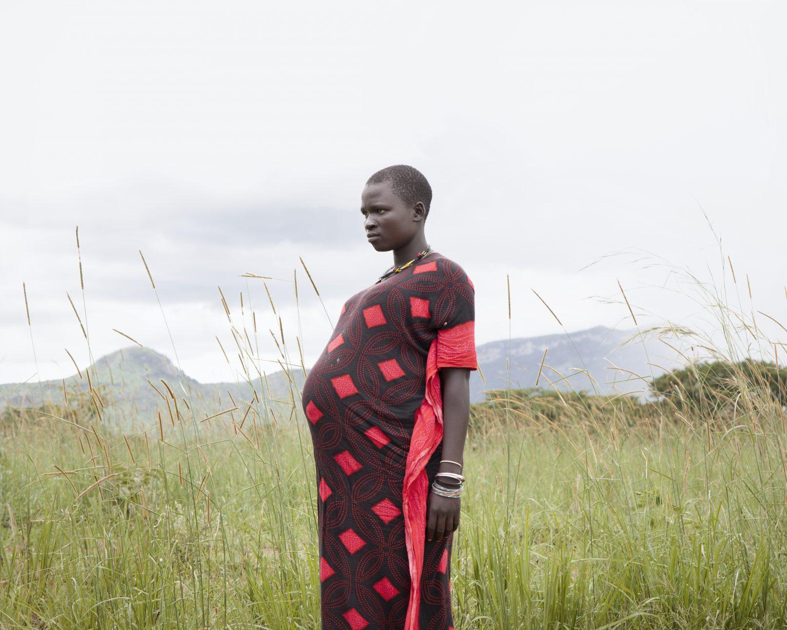 Karamoja region (Uganda). Agnes, 18, is at the end of her ninth month of pregnancy. Behind her, the landscape surrounding the village of Lorengechora. >< Regione della Karamoja (Uganda). Agnes, 18 anni, è alla fine del nono mese di gravidanza. Alle sue spalle, il paesaggio che circonda il villaggio di Lorengechora.
