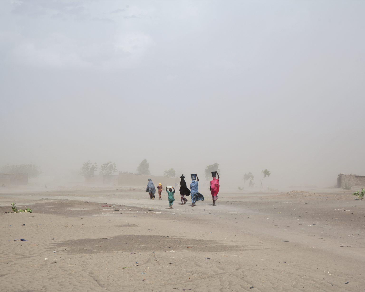 Borno State (Nigeria). Women and their children walk in the middle of a sandstorm on the edge of Gamboru Ngala. The town, near the border with Cameroon, in the past suffered a long siege by the Boko Haram militia. >< Stato di Borno (Nigeria). Alcune donne camminano con i loro bambini in mezzo a una tempesta di sabbia ai confini di Gamboru Ngala. La città, a ridosso del confine con il Camerun, in passato ha subìto un lungo assedio da parte dei miliziani di Boko Haram.